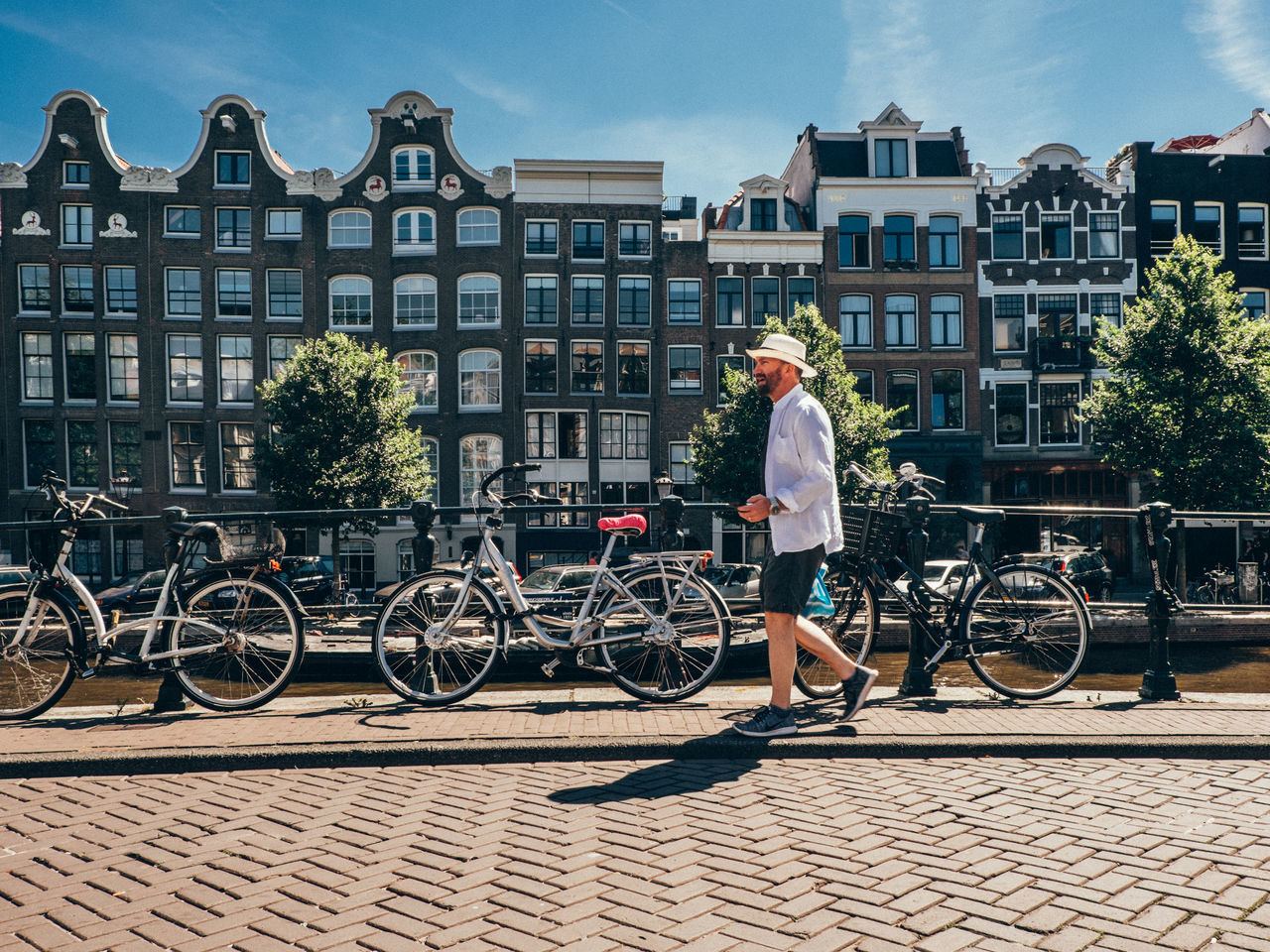 Adult Amsterdam Architecture Bicycle Building Exterior Built Structure Canal Casual Clothing City City Life Day Full Length Leisure Activity Lifestyles Mode Of Transport Netherlands One Person Outdoors Real People Sky Sunlight The Street Photographer - 2017 EyeEm Awards Transportation