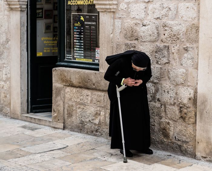 Nun walking slowing through the cobbled streets of Dubrovnik, Croatia Architecture Balck And White Brick Wall Building Building Exterior Built Structure Can City Cobble Stones Day Dubrovnik Elderly Full Length Hanging Out Lifestyles Nun Outdoors Real People Stooped Wall Wall - Building Feature