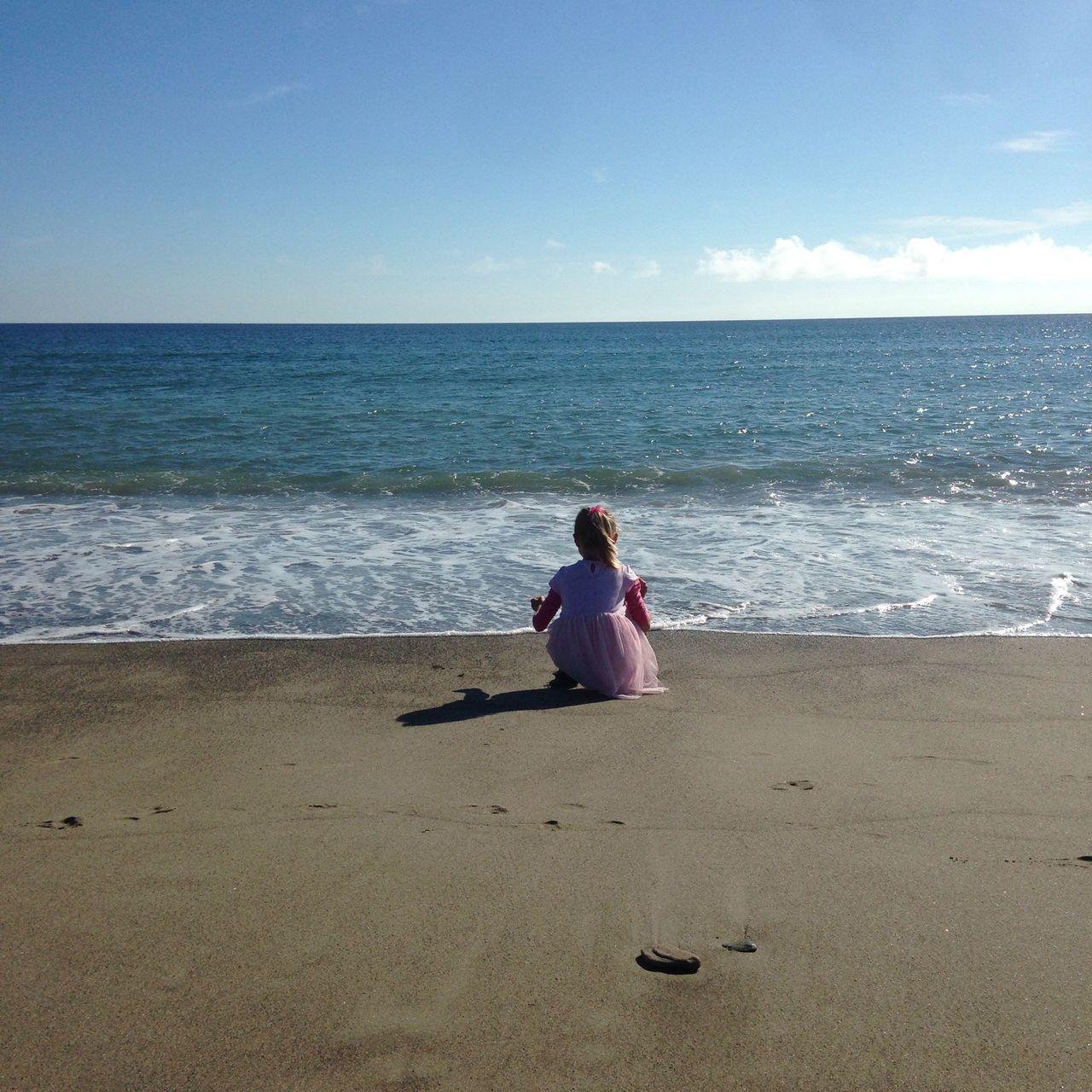 Rear View Of Girl Crouching On Seashore Against Sky