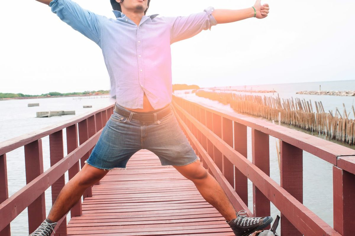 Happiness asian man on wooden bridge Asian  Happiness Happy Man Beauty In Nature Casual Clothing Clear Sky Day Destination Footbridge Human Hand Leisure Activity Lifestyles Low Section Nature One Person Outdoors Real People Sea Sky Standing Sunlight Water Wood - Material Wood Paneling