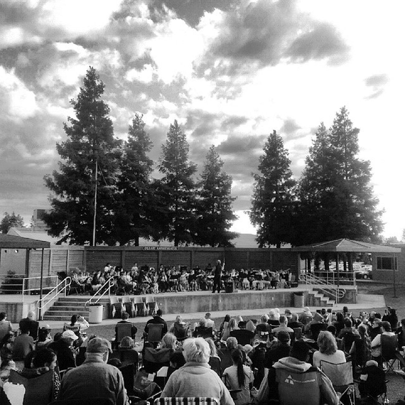 Band recital on a windy night under threatening clouds.