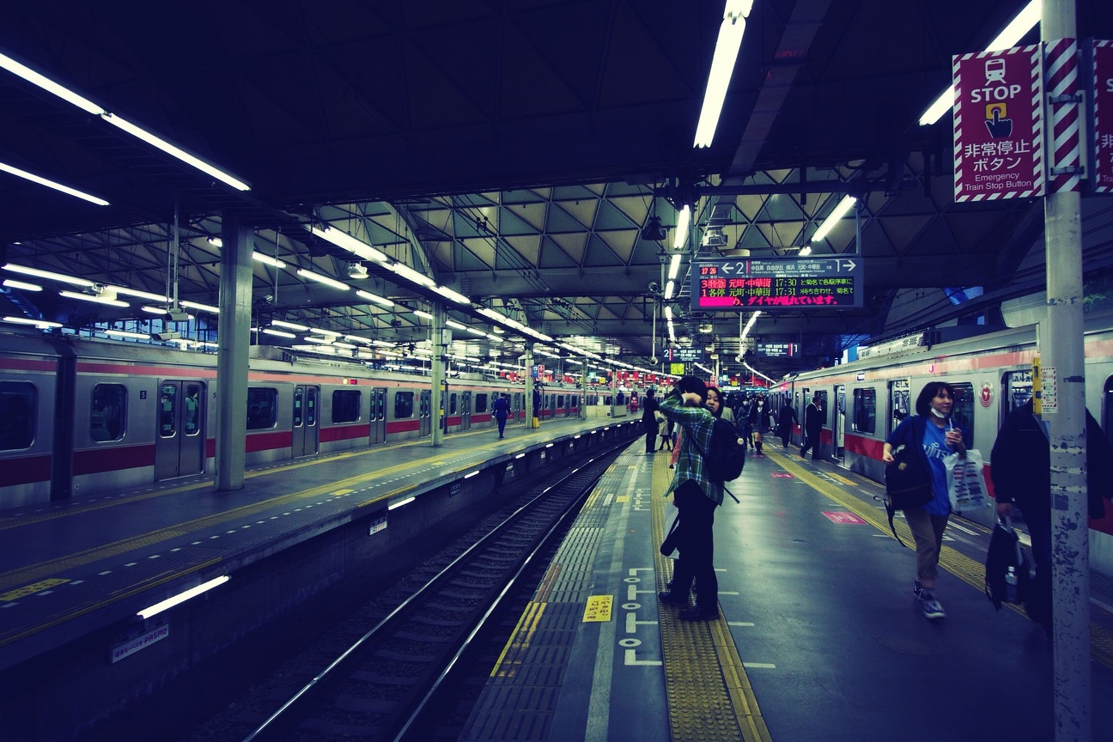 transportation, indoors, railroad station, railroad station platform, public transportation, rail transportation, railroad track, ceiling, men, subway station, illuminated, travel, built structure, architecture, transportation building - type of building, mode of transport, incidental people, person, subway