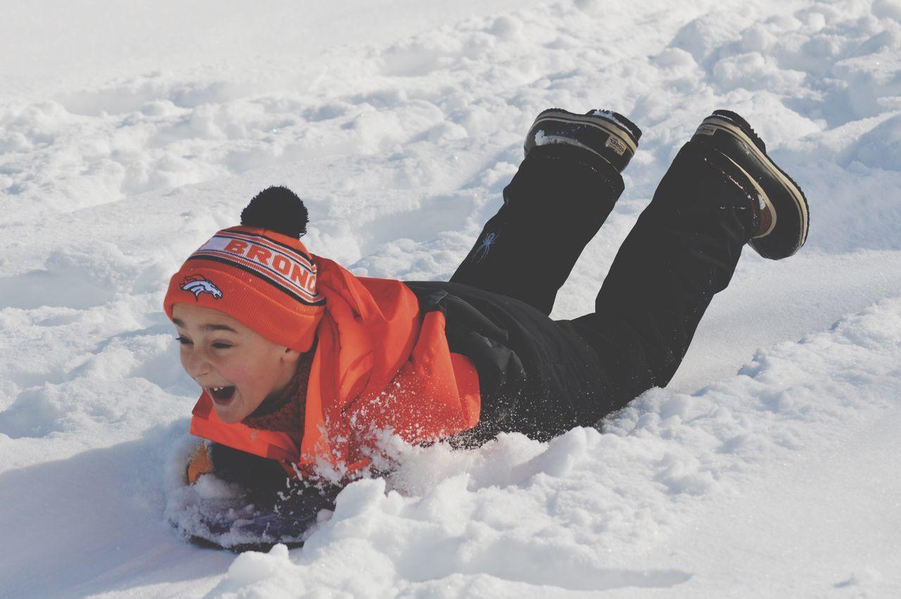 Full Length Of Boy Enjoying On Snowboard