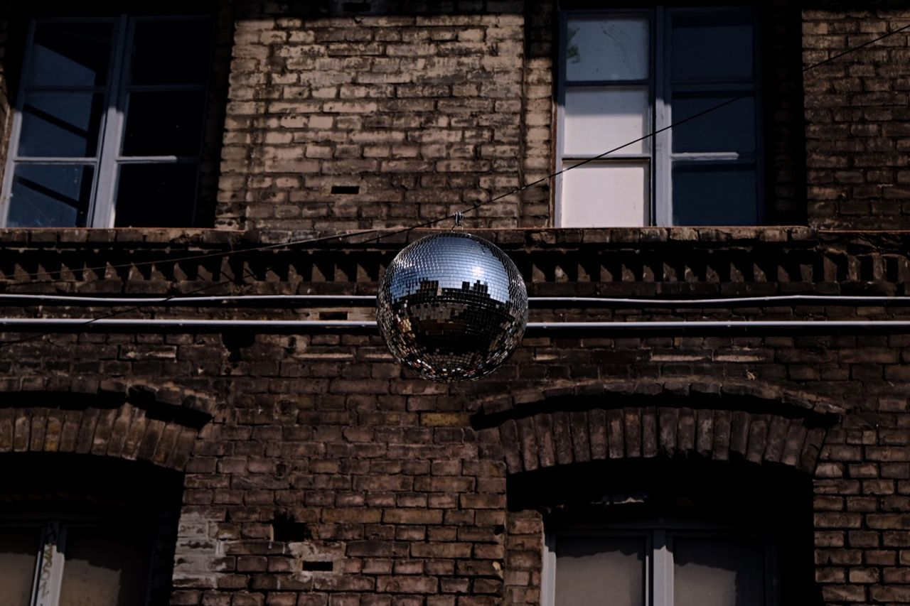 Low Angle View Of Disco Ball Hanging Against Old Building