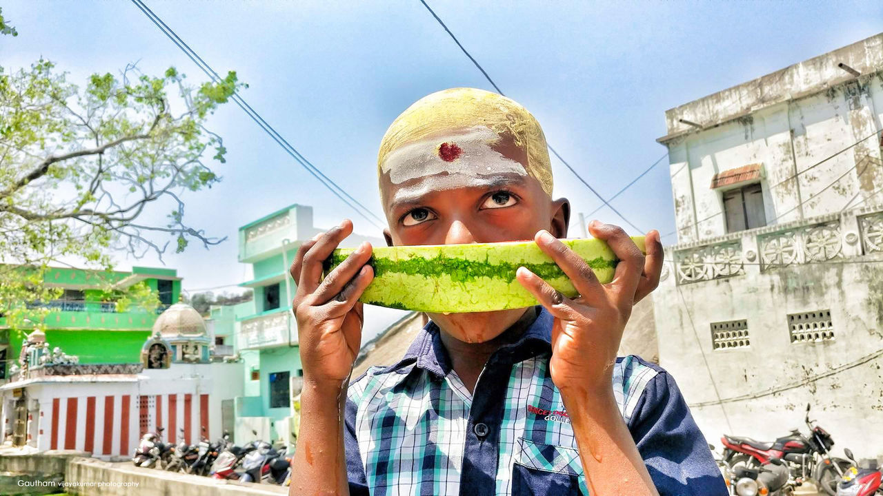 Architecture Building Exterior Built Structure Casual Clothing City Close-up Day Food Freshness Front View Fruits Headshot Holding Lifestyles Live For The Story Looking At Camera One Person Outdoors People Portrait Real People Sky Summer Watermelon Young Adult