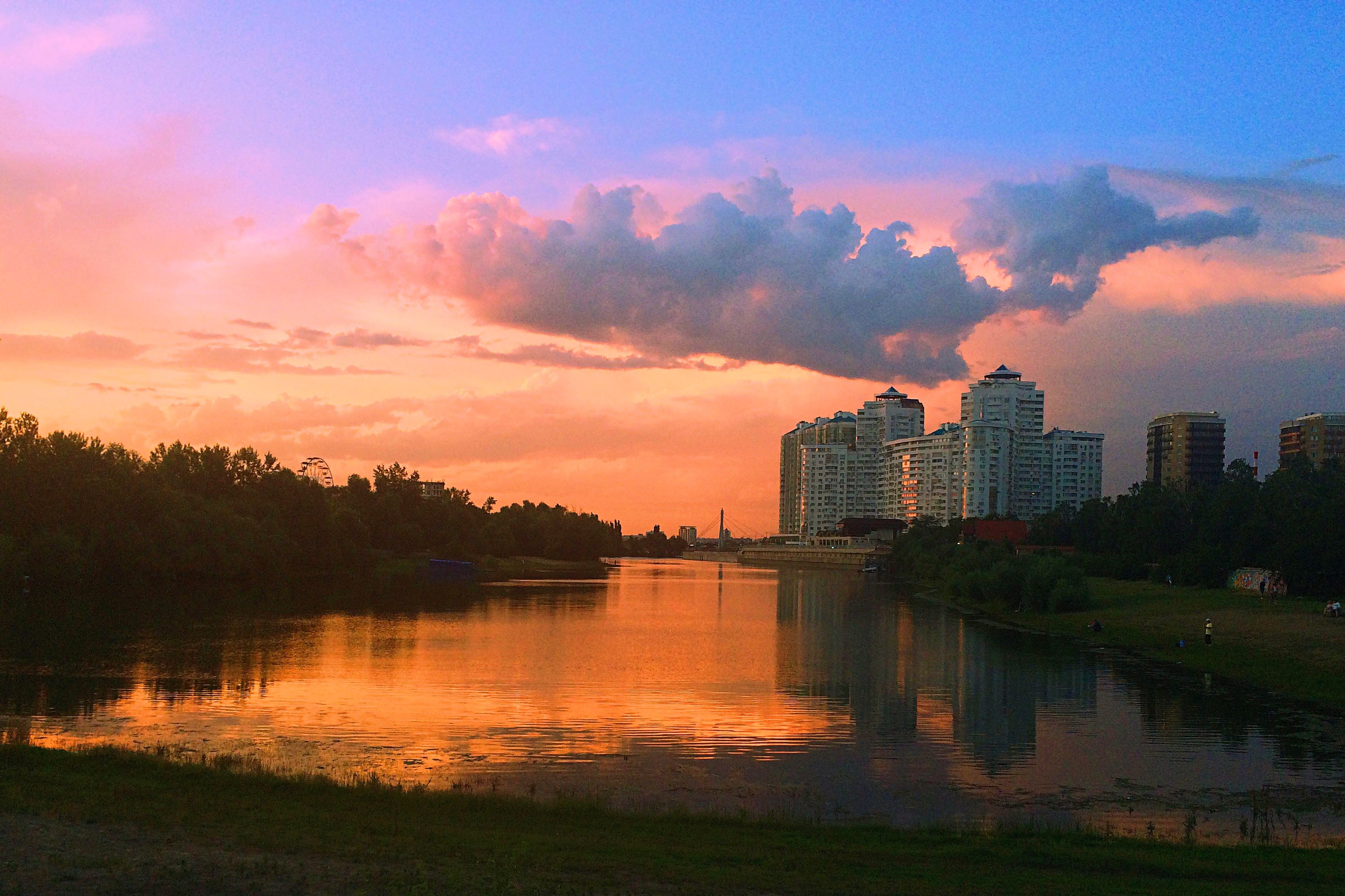 sunset, building exterior, architecture, water, built structure, sky, reflection, cloud - sky, tree, lake, river, city, waterfront, orange color, cloud, silhouette, scenics, beauty in nature, tranquility, nature