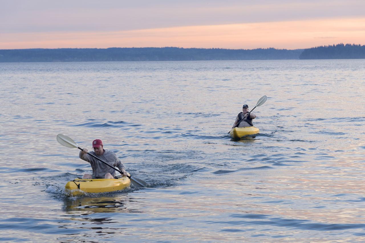 Two adults paddling kayaks at sunset Adults Adventure Kayak Lake Ocean Outdoors Paddle Recreational Pursuit Sea Sports Sunset Two People