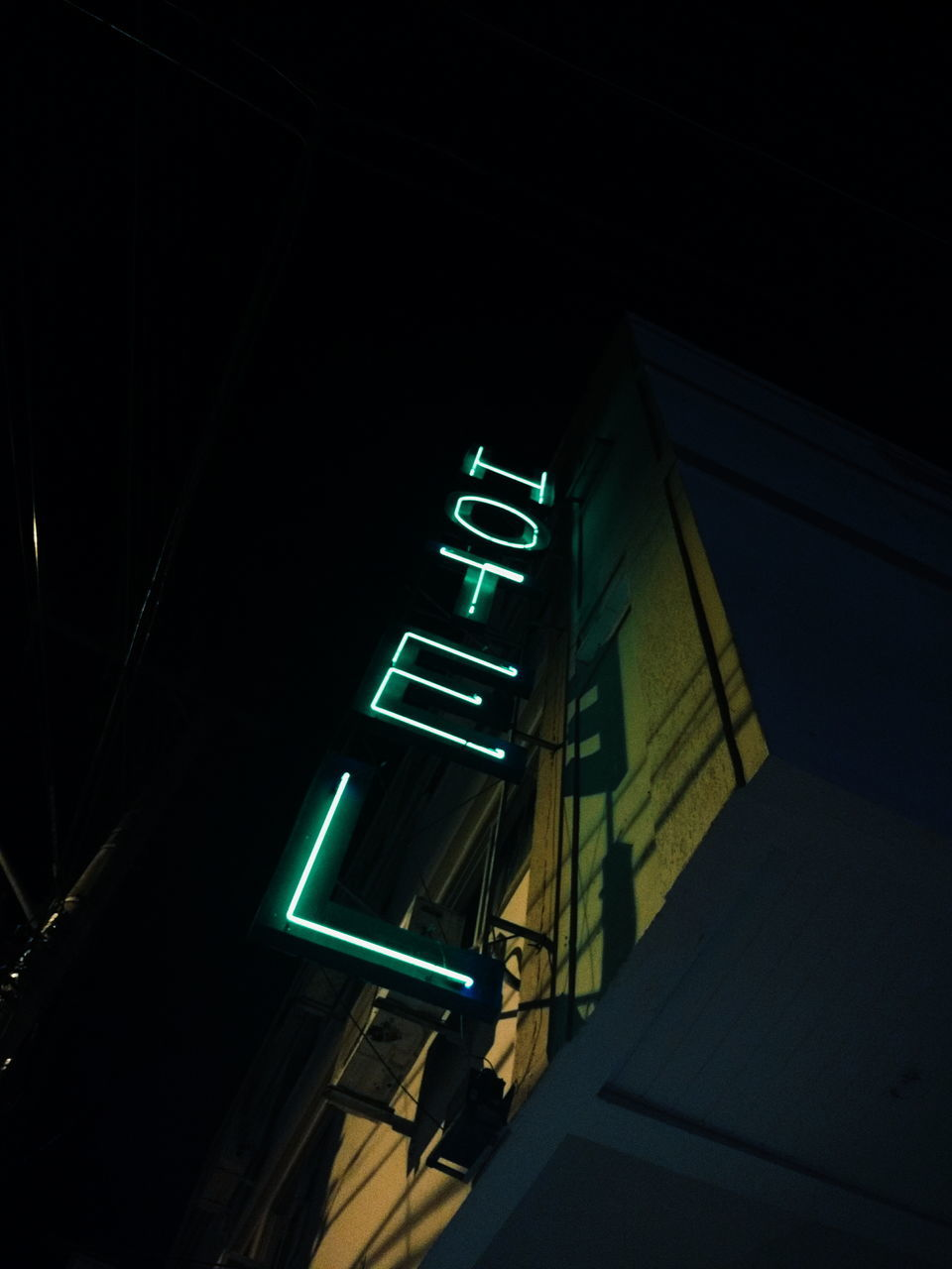 illuminated, low angle view, night, built structure, architecture, no people, green color, communication, building exterior, neon, guidance, outdoors, city, sky