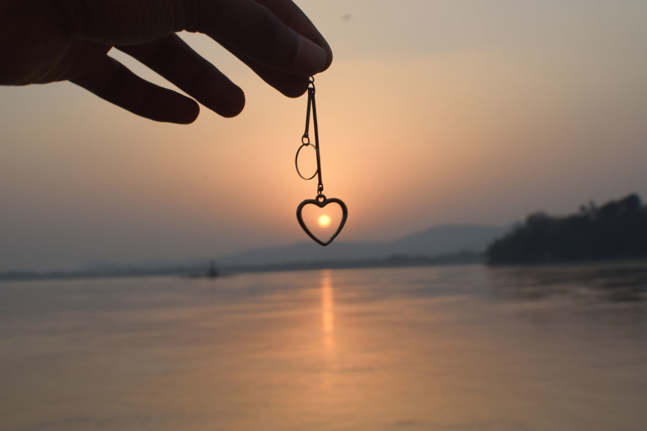 sunset, human hand, sky, water, human body part, hanging, outdoors, silhouette, beauty in nature, nature, reflection, real people, scenics, waterfront, sun, sea, one person, gold colored, close-up, day, people