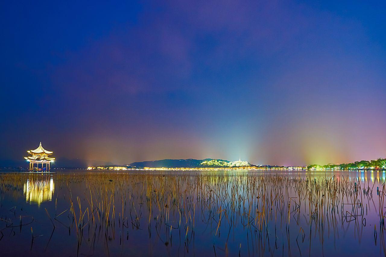 Illuminated Gazebo On Lake Against Sky At Night