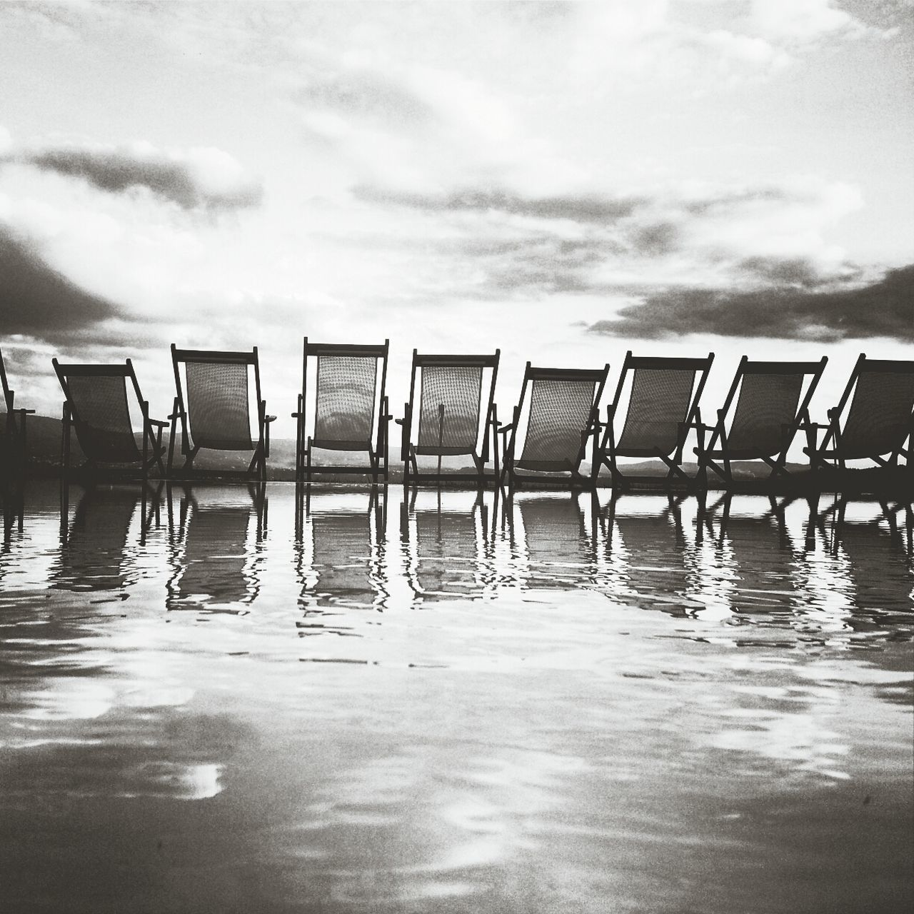 Reflection Of Chairs In A Pool