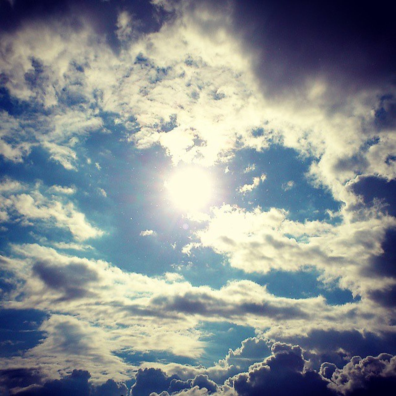 sunbeam, nature, beauty in nature, sky, sun, cloud - sky, scenics, sunlight, tranquility, cloudscape, majestic, low angle view, vibrant color, no people, backgrounds, tranquil scene, sky only, day, outdoors, full frame, blue