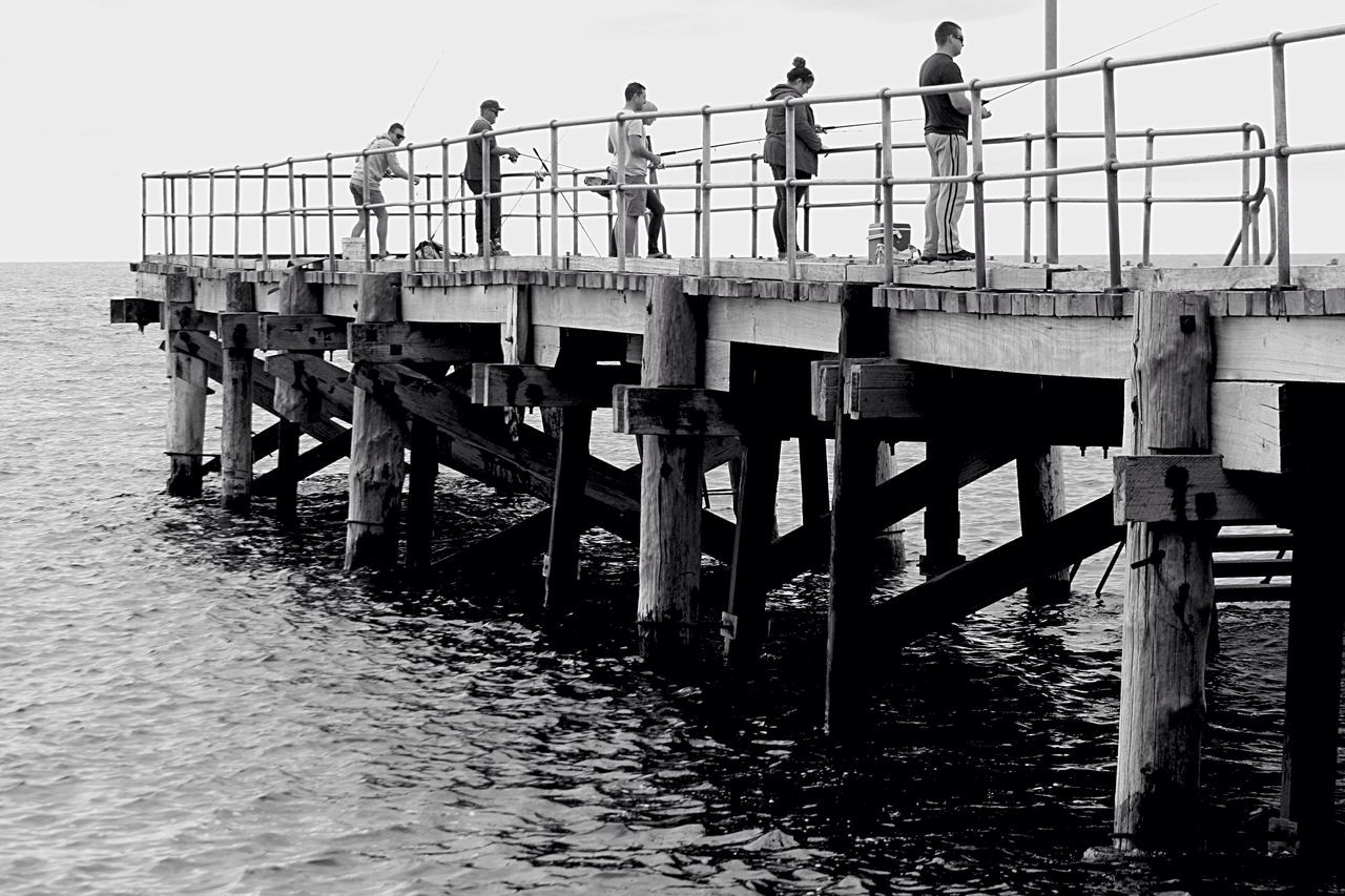 People Standing On Pier While Fishing In Sea