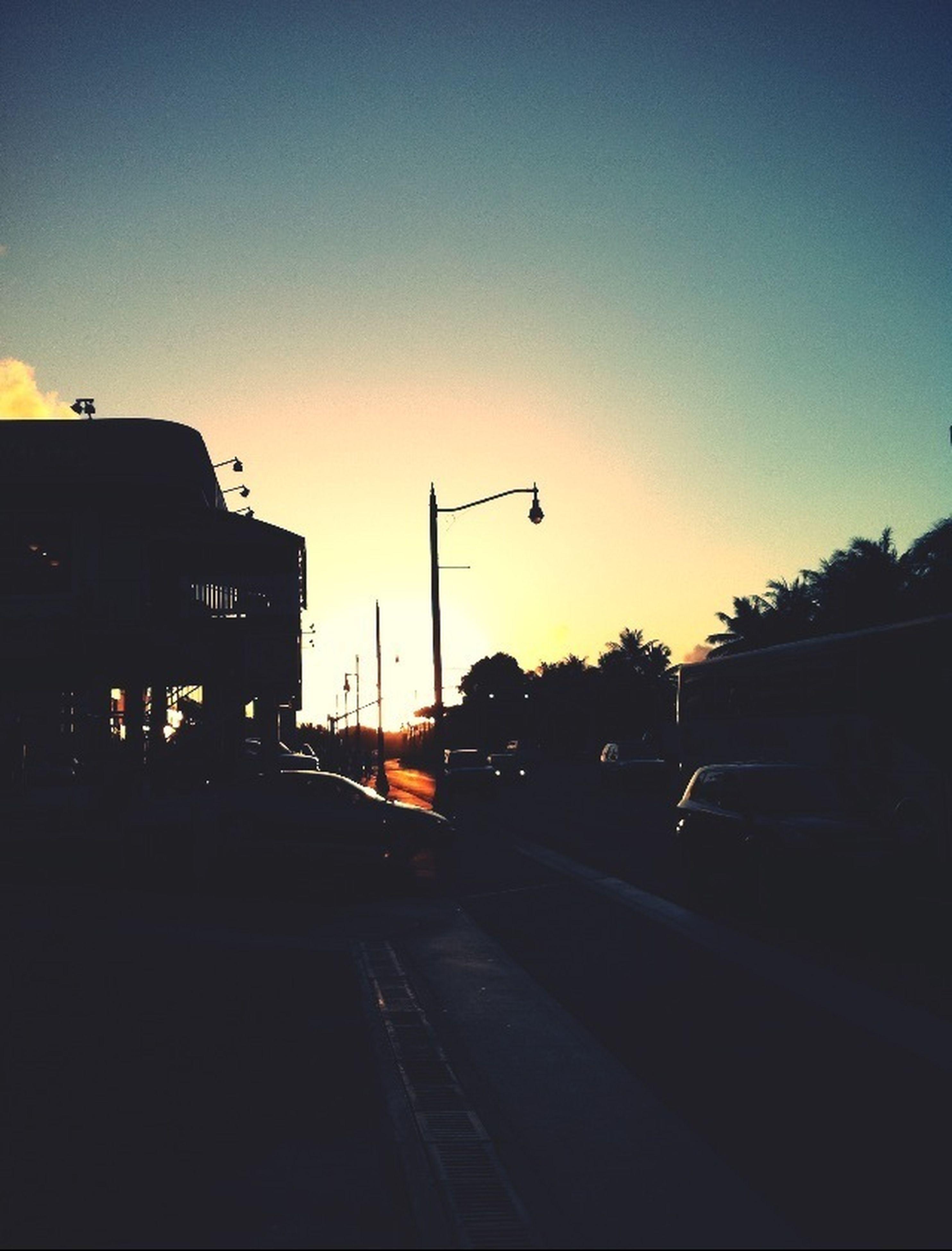 sunset, transportation, clear sky, street light, car, silhouette, building exterior, street, built structure, copy space, land vehicle, architecture, road, mode of transport, city, tree, sun, sky, orange color, traffic