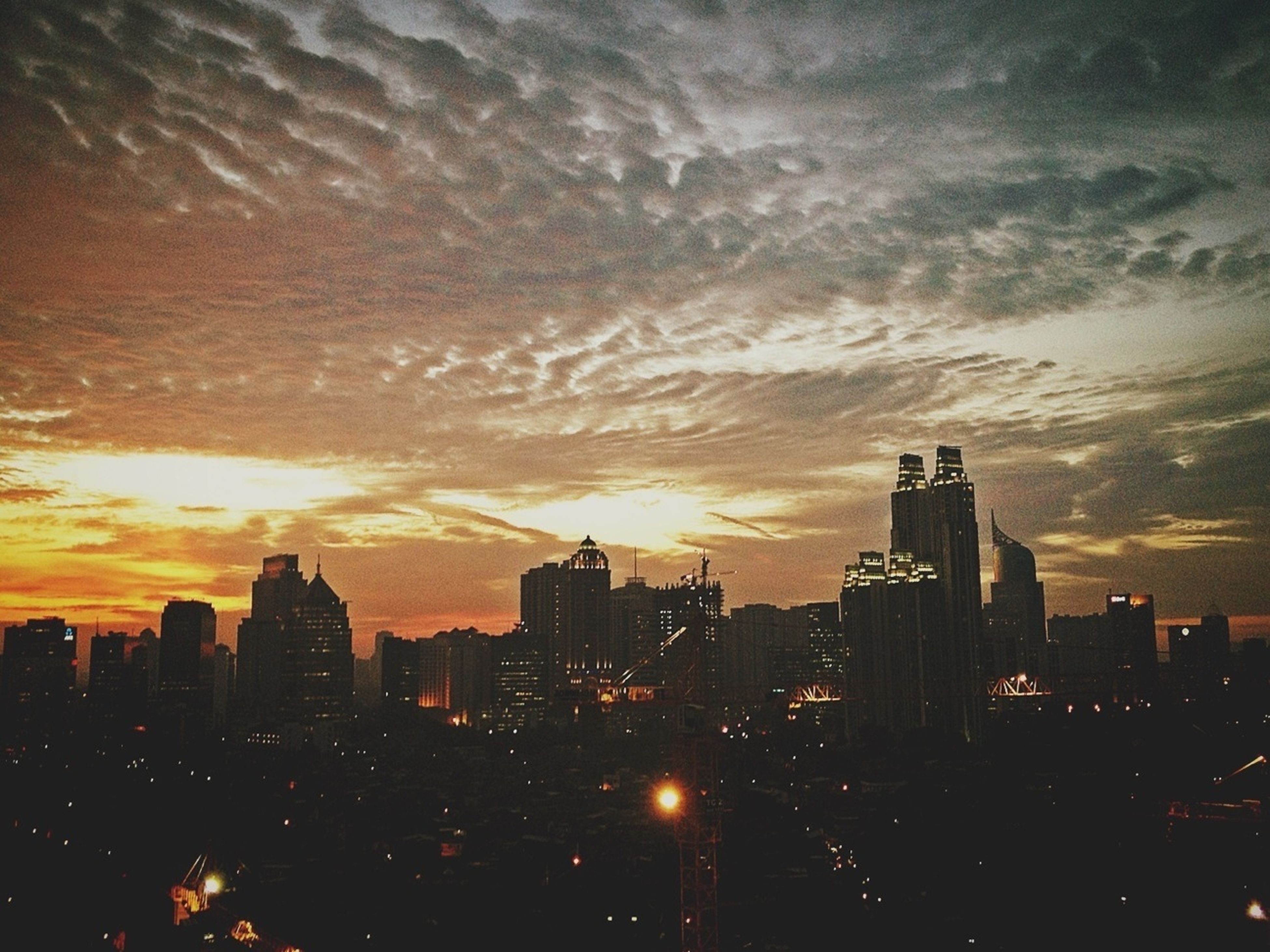 building exterior, city, sunset, architecture, cityscape, built structure, skyscraper, sky, silhouette, orange color, urban skyline, cloud - sky, tall - high, city life, tower, office building, residential building, crowded, modern, residential district