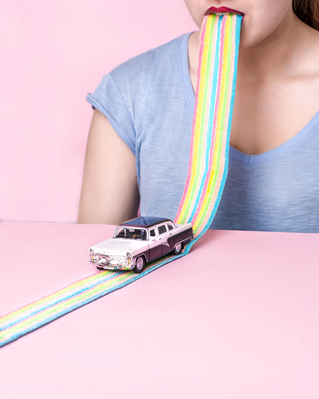 Woman With Toy Car Track In Mouth Against Pink Background