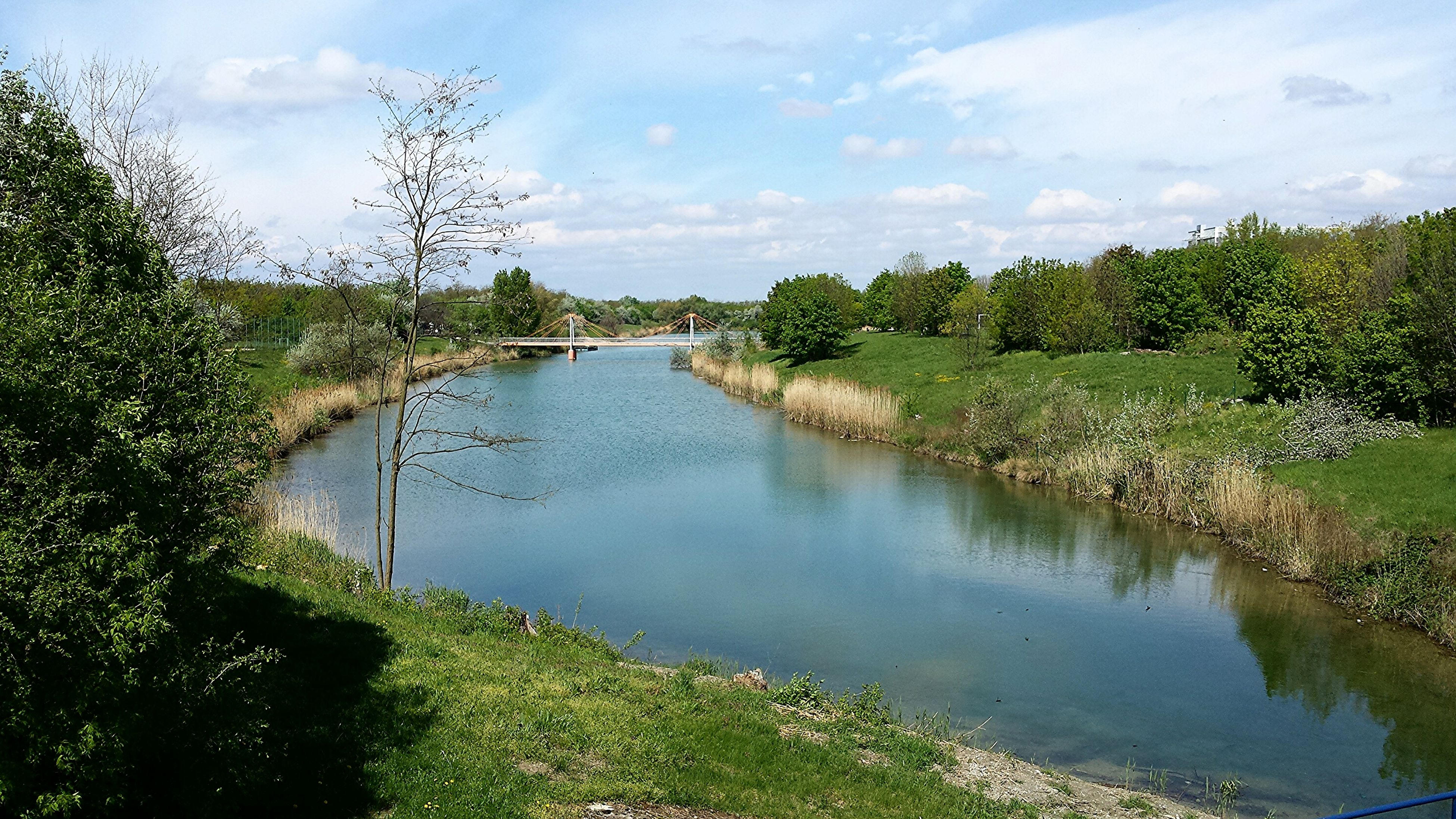 water, sky, tranquility, tranquil scene, green color, grass, nature, growth, plant, tree, scenics, beauty in nature, river, reflection, cloud - sky, lake, panoramic, day, cloud, stream
