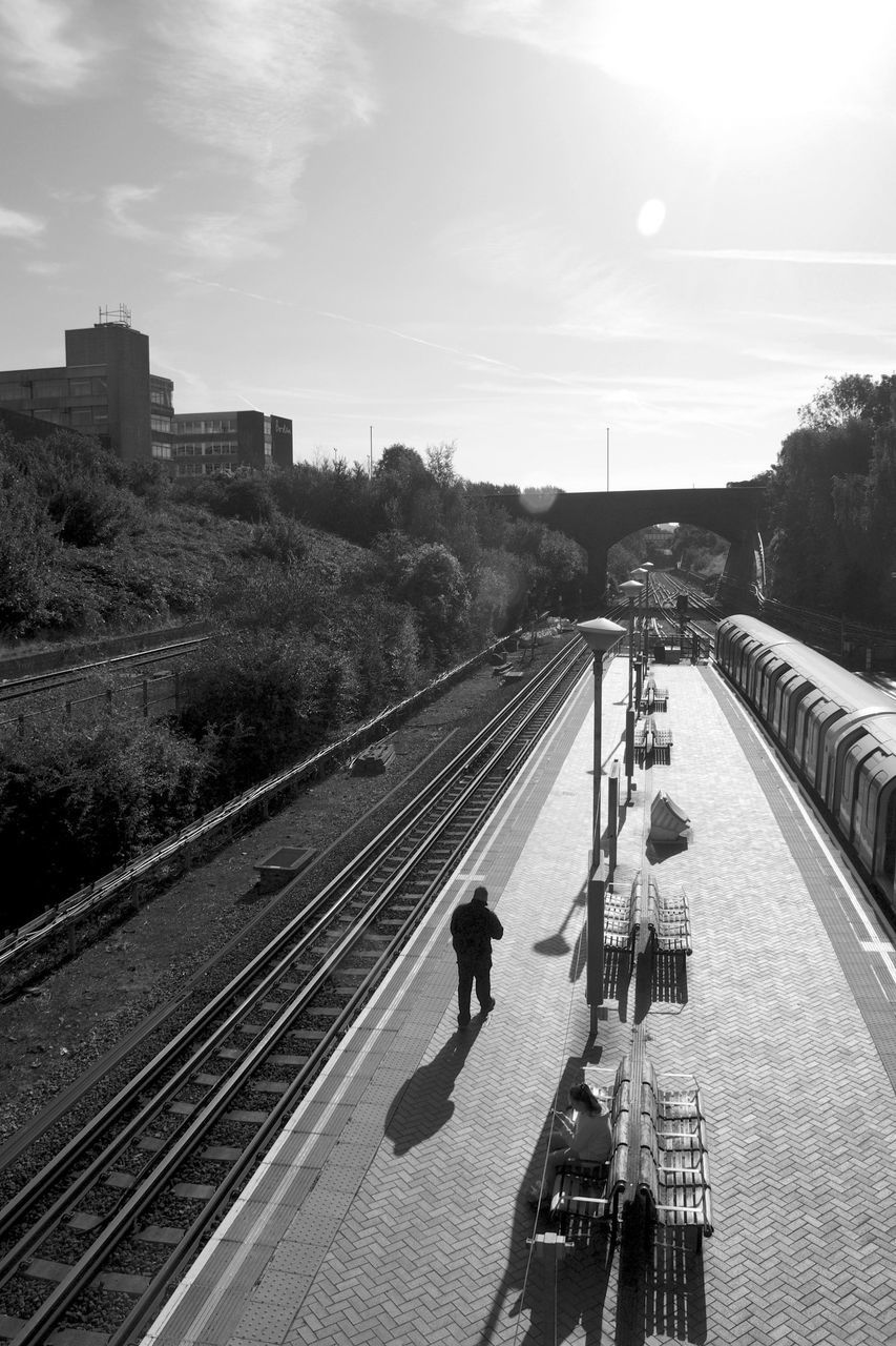 high angle view, full length, railroad track, real people, men, transportation, rail transportation, sky, two people, walking, outdoors, day, architecture, railroad station platform, built structure, lifestyles, city, tree, adult, people