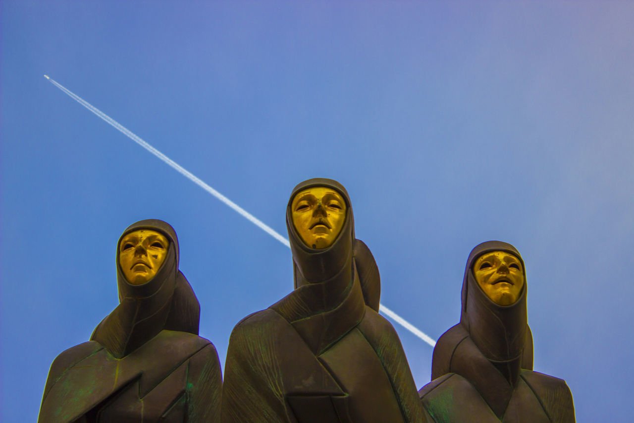 statue, human representation, low angle view, sculpture, art and craft, gold colored, clear sky, religion, outdoors, spirituality, no people, day, sky