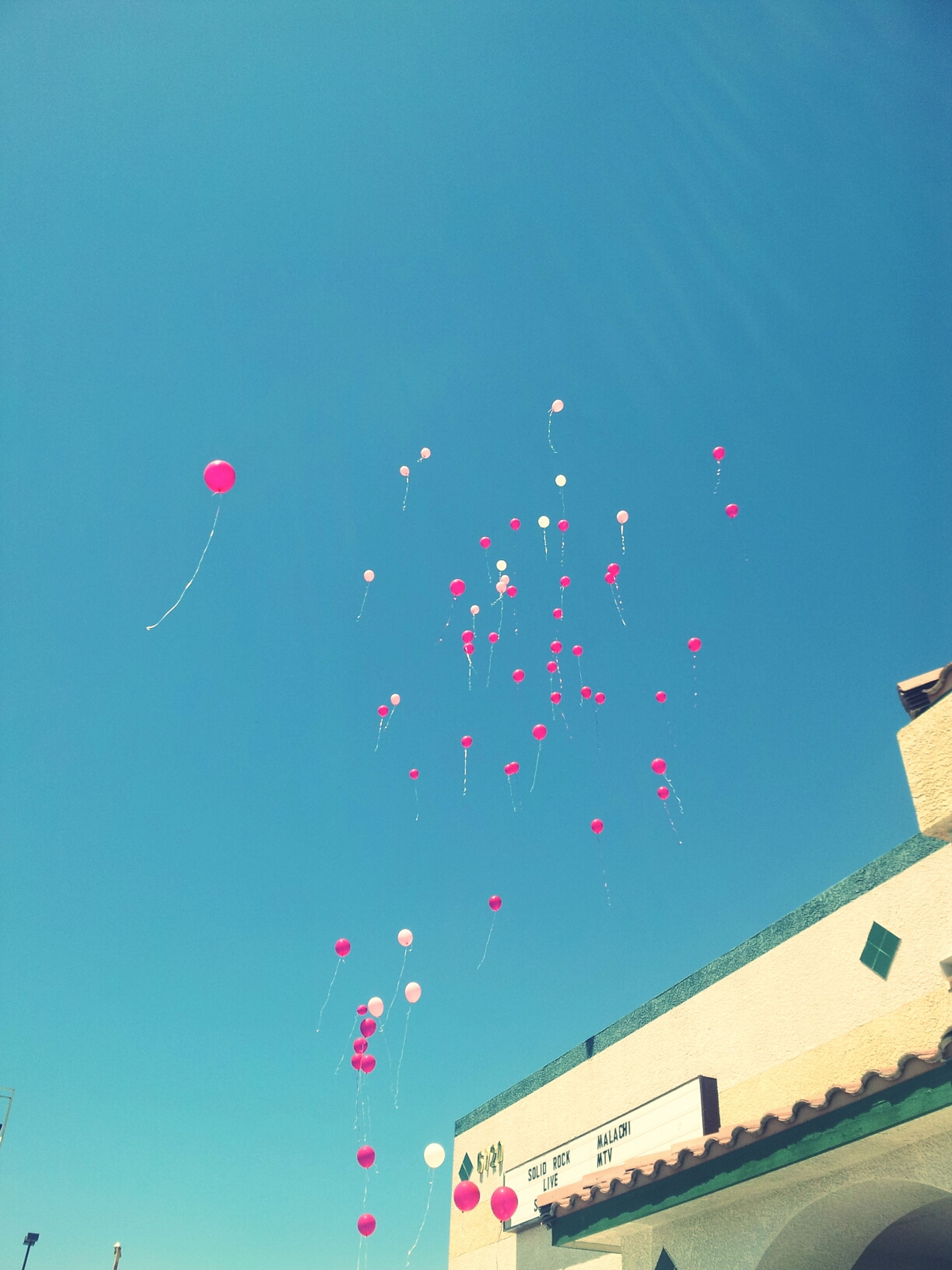 clear sky, low angle view, multi colored, blue, copy space, celebration, illuminated, flying, decoration, night, mid-air, built structure, lighting equipment, outdoors, architecture, pink color, building exterior, sky, no people, balloon