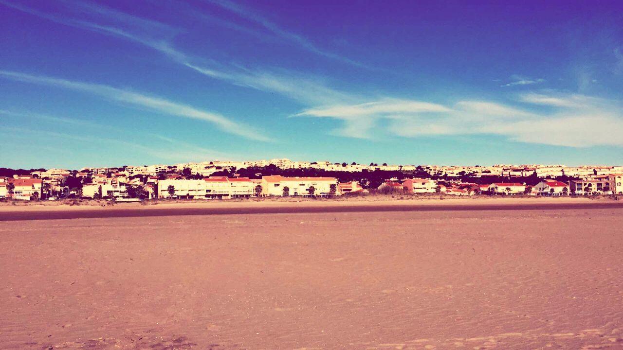 Houses By Sandy Beach Against Sky
