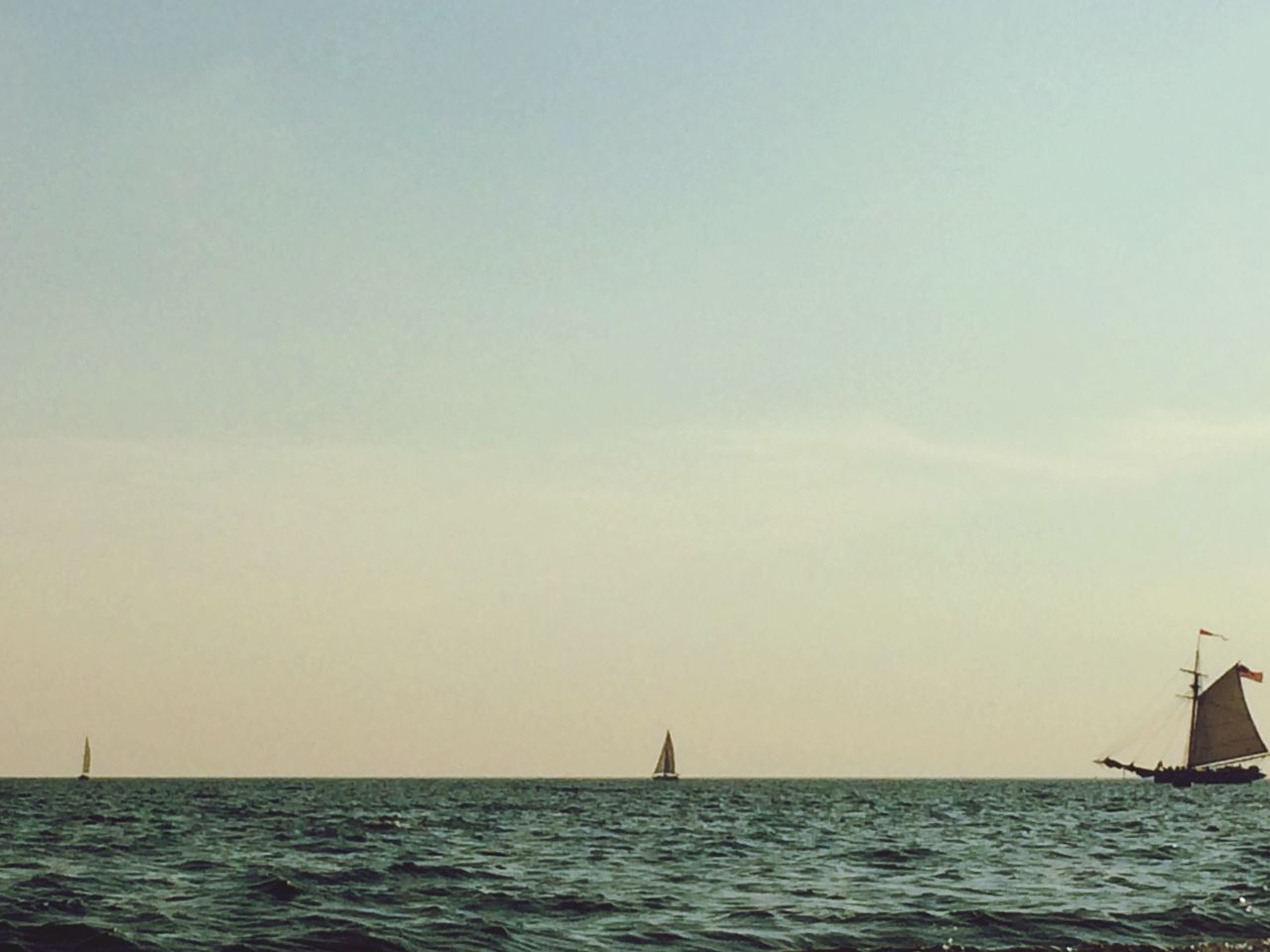 Distance Shot Of Boats In Calm Blue Sea
