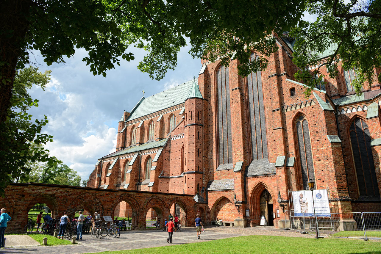 Outside of Doberan Minster (Germany). People walking outside at Bad Doberan Minster in summer time. Arch Architecture Bad Doberan Building Exterior Built Structure City Cloud Cloud - Sky Day Façade Grass Green Color History Lawn Lifestyles Mecklenburg-Vorpommern Outdoors Sky Tourism Travel Destinations Tree