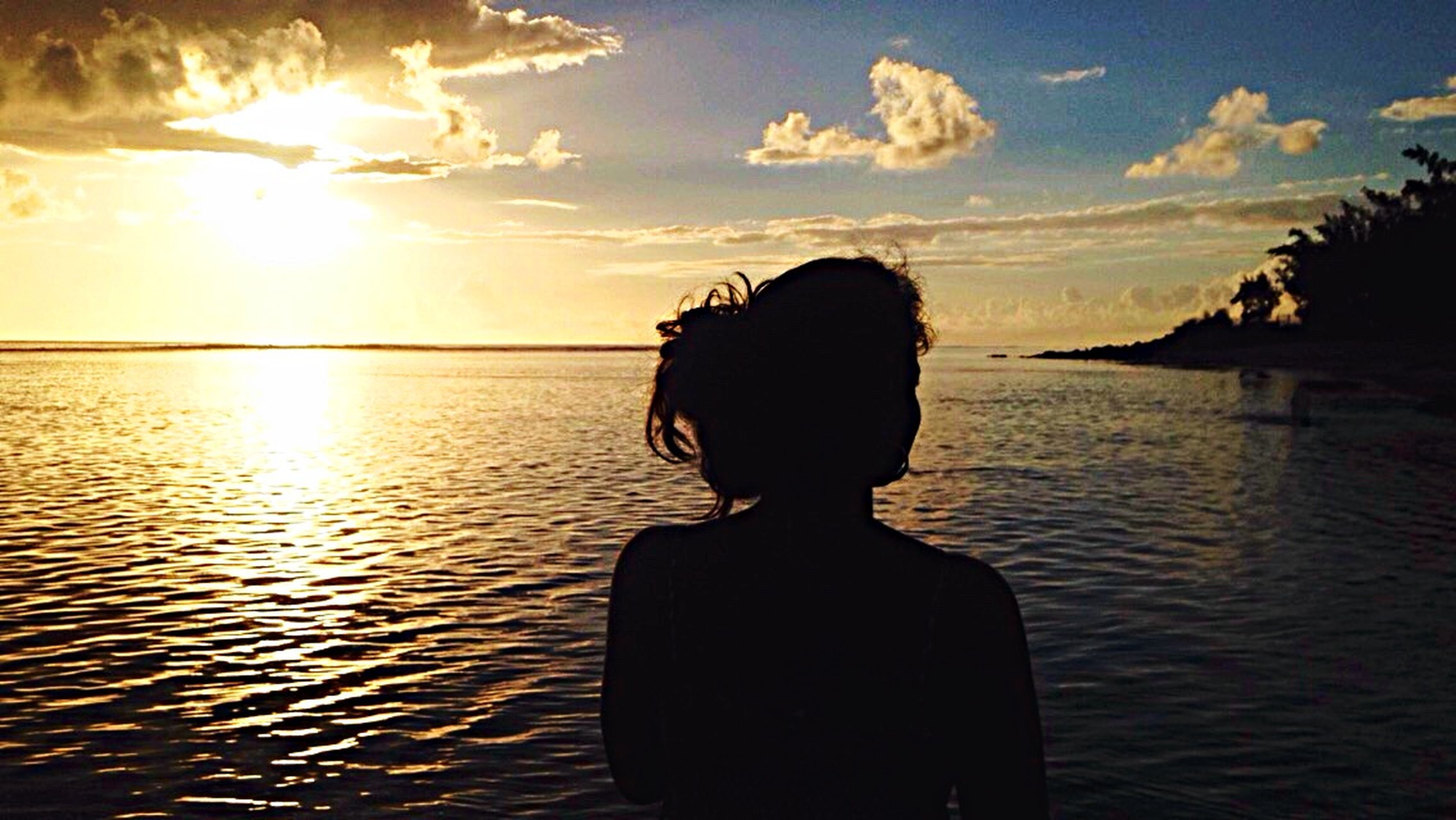 water, sunset, lifestyles, standing, silhouette, sea, rear view, sky, leisure activity, sun, tranquility, person, scenics, three quarter length, tranquil scene, beauty in nature, waist up, nature