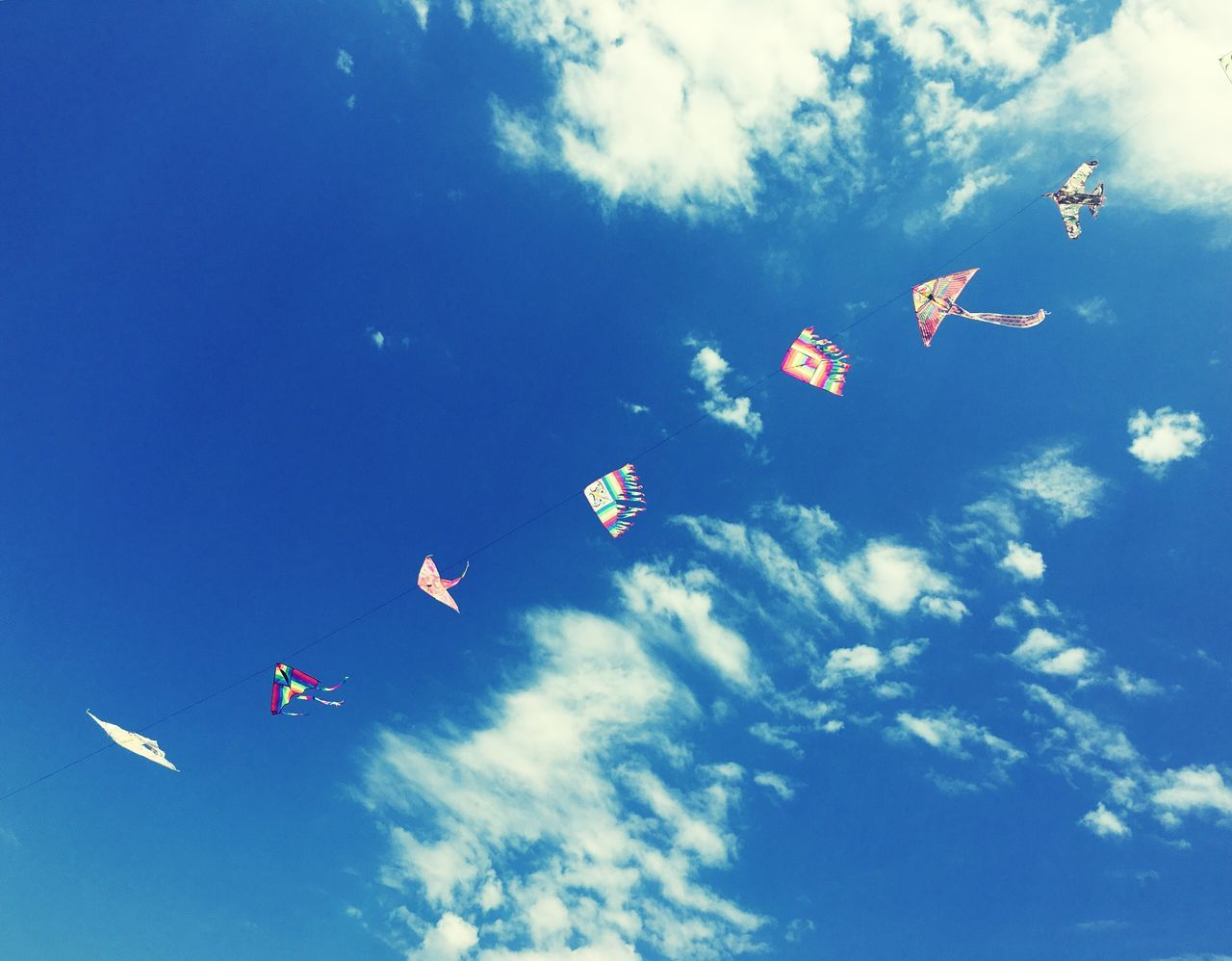 flag, patriotism, flying, sky, low angle view, kite, wind, mid-air, kite - toy, cloud - sky, pride, childhood, day, no people, blue, outdoors, nature, beauty in nature