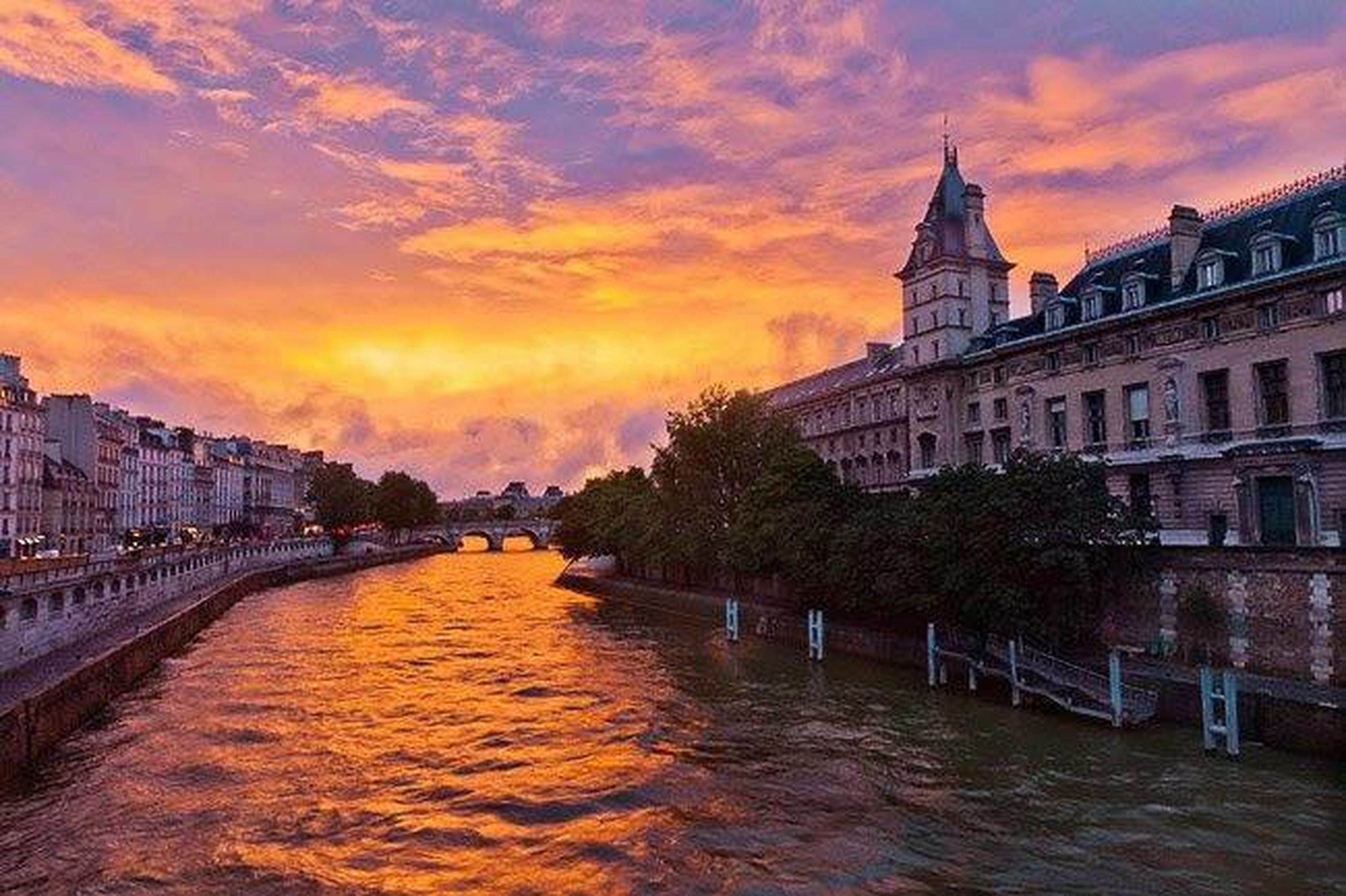 architecture, building exterior, built structure, sunset, water, sky, orange color, waterfront, city, cloud - sky, canal, river, cloud, building, residential building, residential structure, travel destinations, cloudy, outdoors, reflection