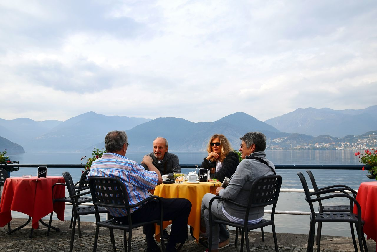 table, mountain, chair, mountain range, restaurant, food and drink, outdoor cafe, togetherness, friendship, cafe, nature, sky, day, scenics, men, real people, outdoors, lake, relaxation, water, place setting, women, beauty in nature, food, people
