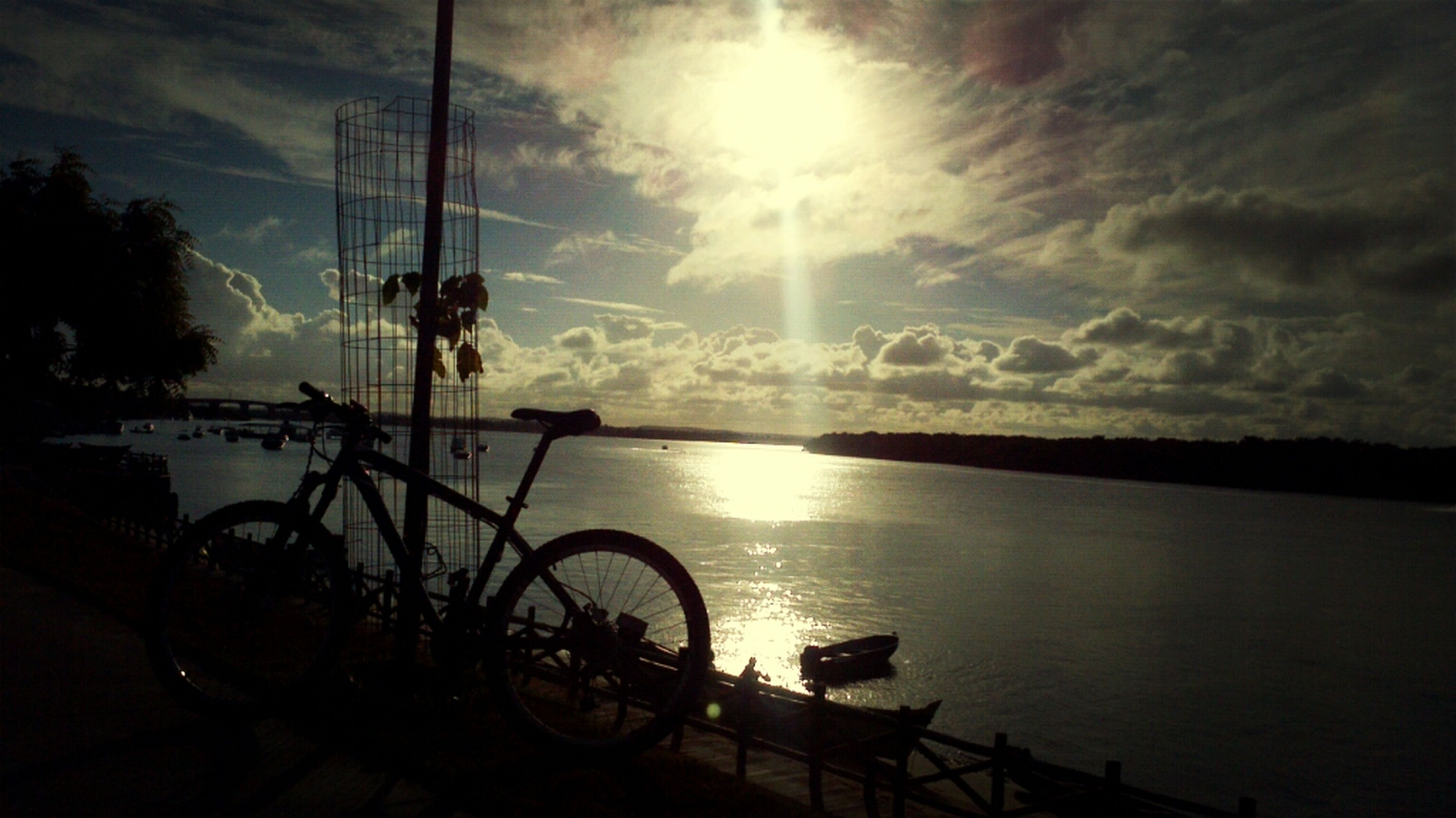 sun, bicycle, sky, transportation, mode of transport, water, cloud - sky, sunbeam, sunlight, scenics, tranquility, tranquil scene, reflection, beauty in nature, sea, silhouette, nature, land vehicle, sunset, stationary