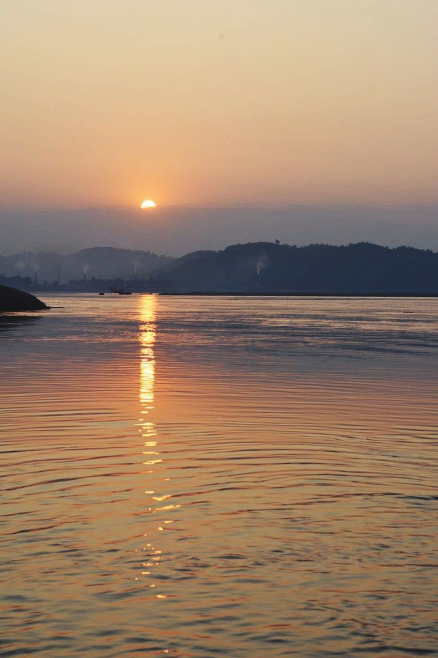 sunset, scenics, beauty in nature, nature, tranquility, tranquil scene, water, orange color, sea, holiday, reflection, outdoors, no people, sky, silhouette, mountain, sun, waterfront, beach