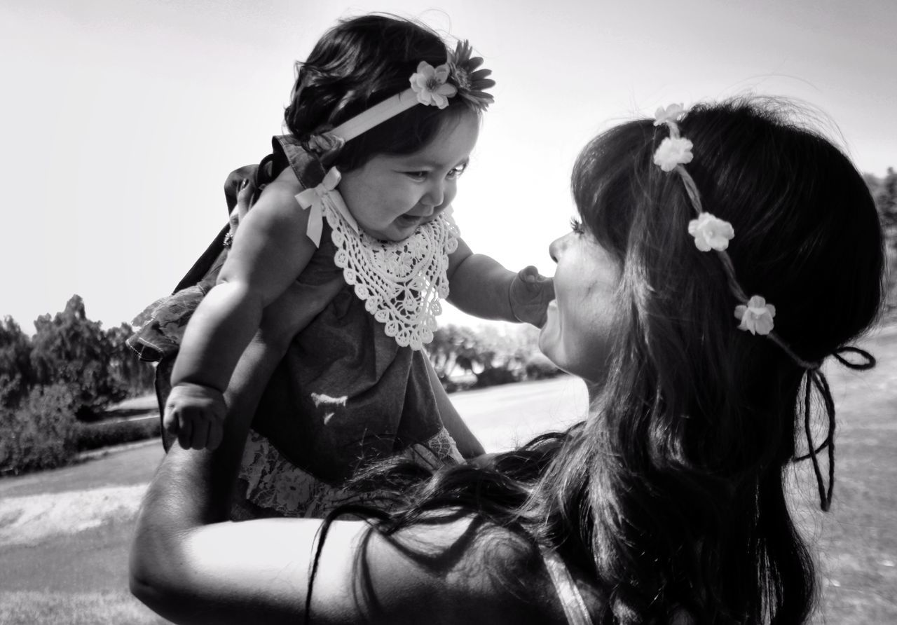 real people, togetherness, love, bonding, two people, childhood, leisure activity, lifestyles, field, outdoors, young women, wearing flowers, girls, happiness, day, elementary age, groom, young adult, friendship, sky, bride, tree, flower, nature, mammal