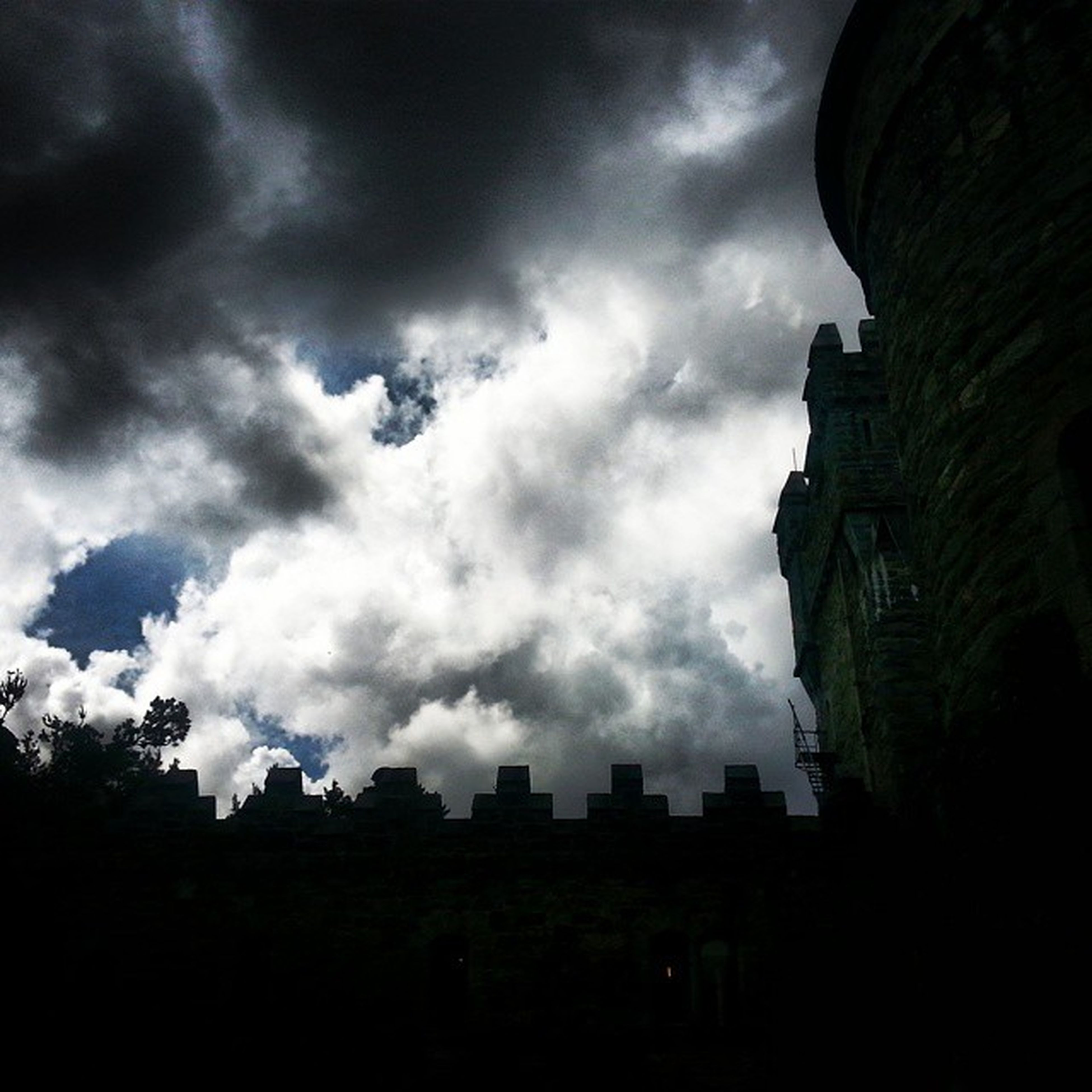 sky, building exterior, architecture, built structure, cloud - sky, cloudy, low angle view, silhouette, cloud, overcast, weather, building, dusk, city, outdoors, storm cloud, tree, no people, residential building, day