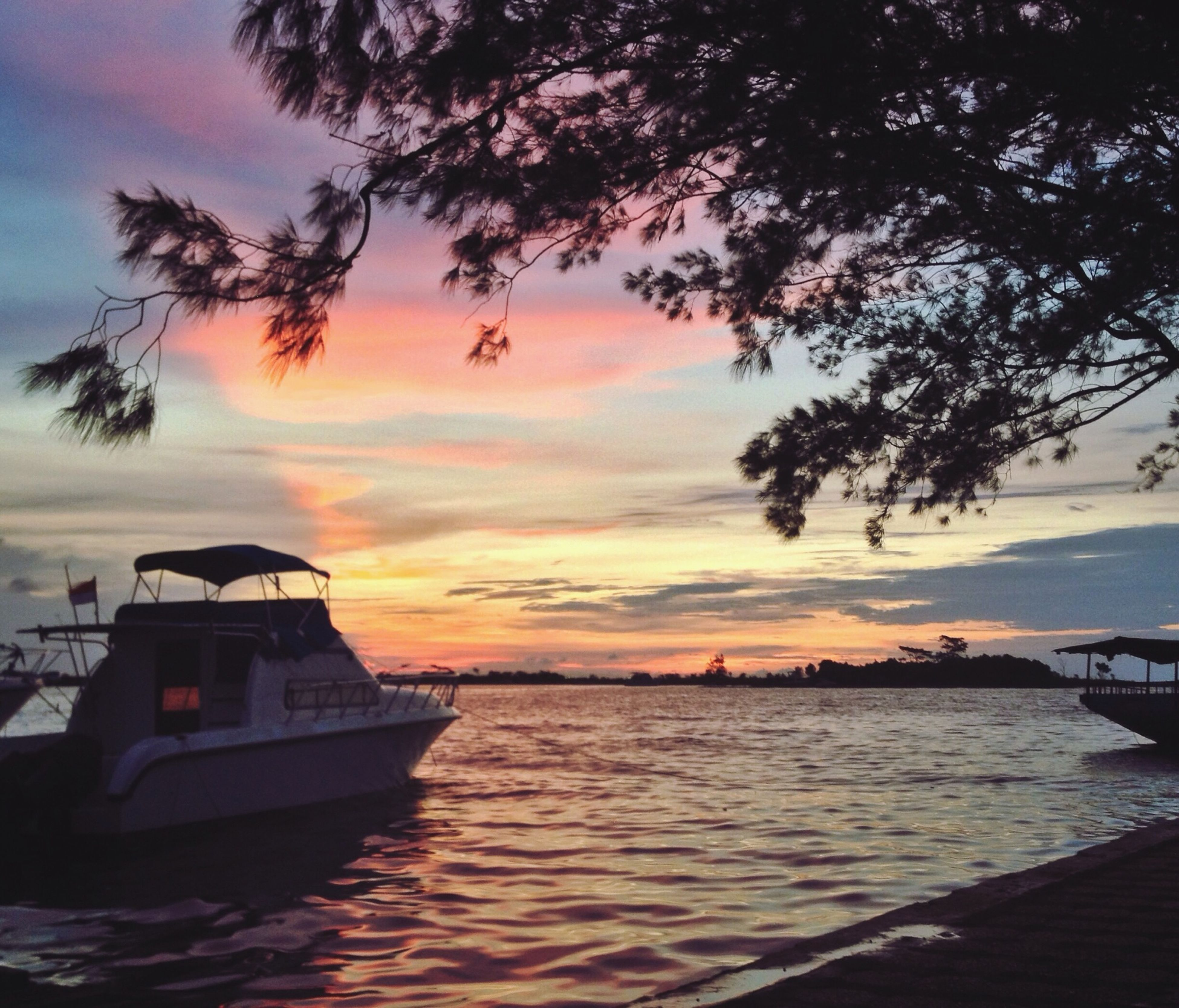 sunset, water, sky, sea, cloud - sky, scenics, tranquility, tranquil scene, waterfront, beauty in nature, tree, orange color, nature, nautical vessel, transportation, cloud, idyllic, boat, silhouette, horizon over water