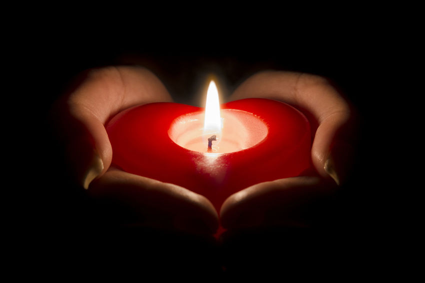 Woman's hands holding a heart shaped candle in the dark Black Background Burning Sky Candle Dark Faith Flame Isolated Love Red Romance Romantic Valentine's Day  Woman Belief Candlelight Gift Giving Heart Shape Holding Human Hand Illuminated Night Passion Trust Wish