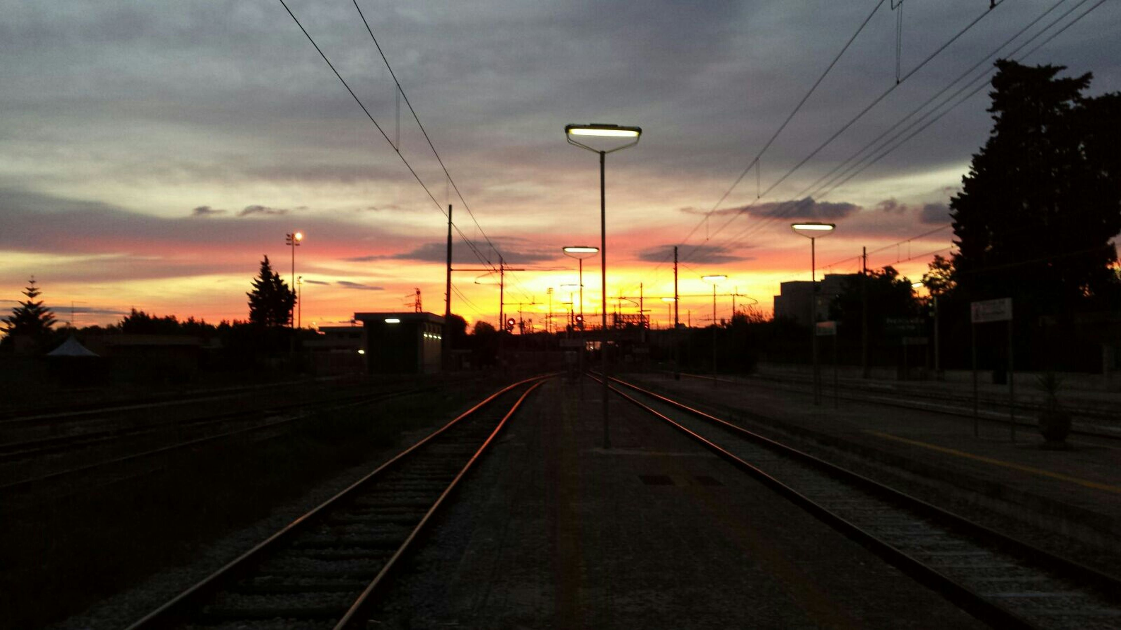 railroad track, rail transportation, transportation, sunset, public transportation, railroad station, railroad station platform, sky, power line, electricity pylon, cloud - sky, the way forward, train - vehicle, diminishing perspective, electricity, railway track, cable, travel, power supply, vanishing point