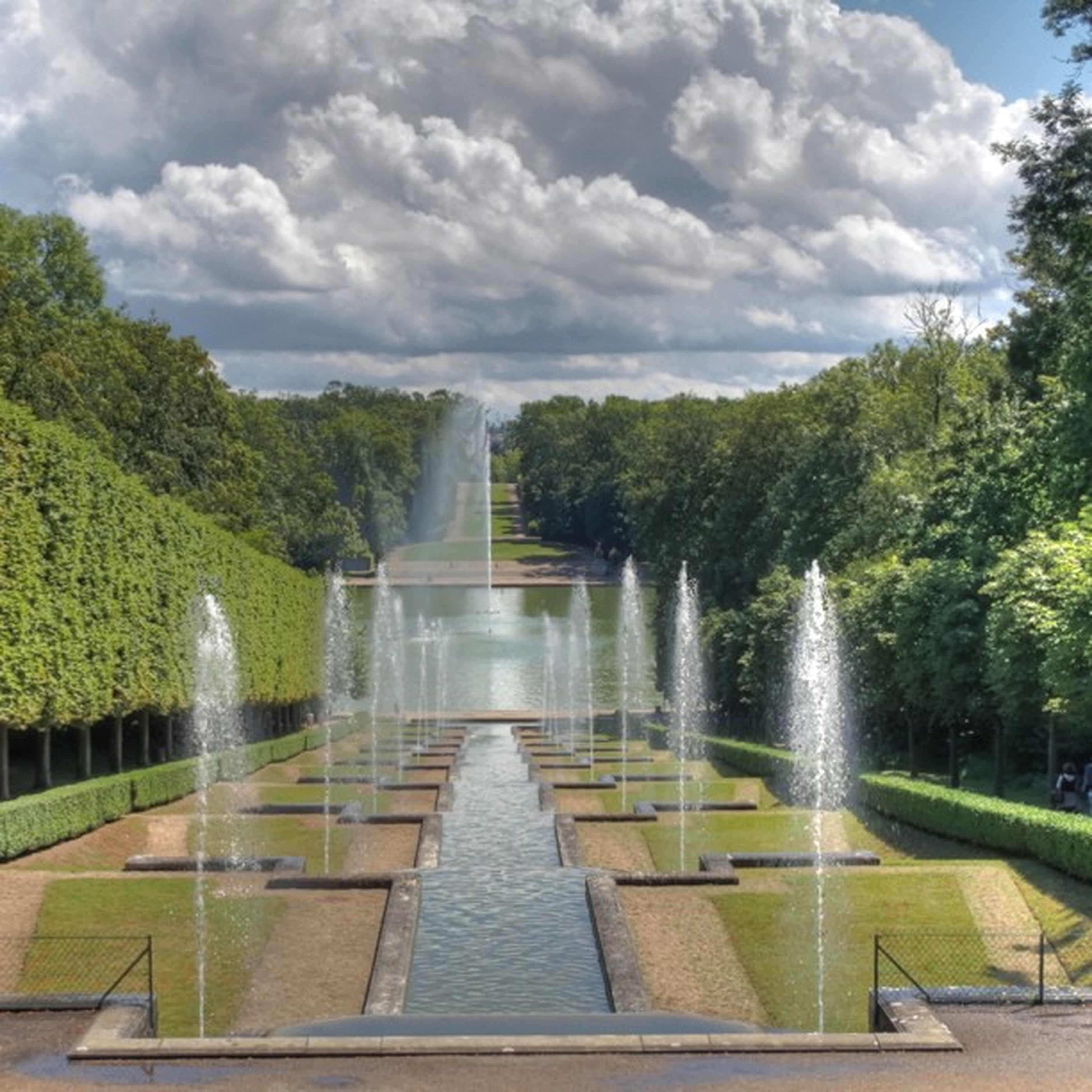 water, tree, sky, cloud - sky, built structure, fountain, architecture, green color, cloudy, nature, river, beauty in nature, cloud, railing, day, scenics, growth, bridge - man made structure, park - man made space, tranquility