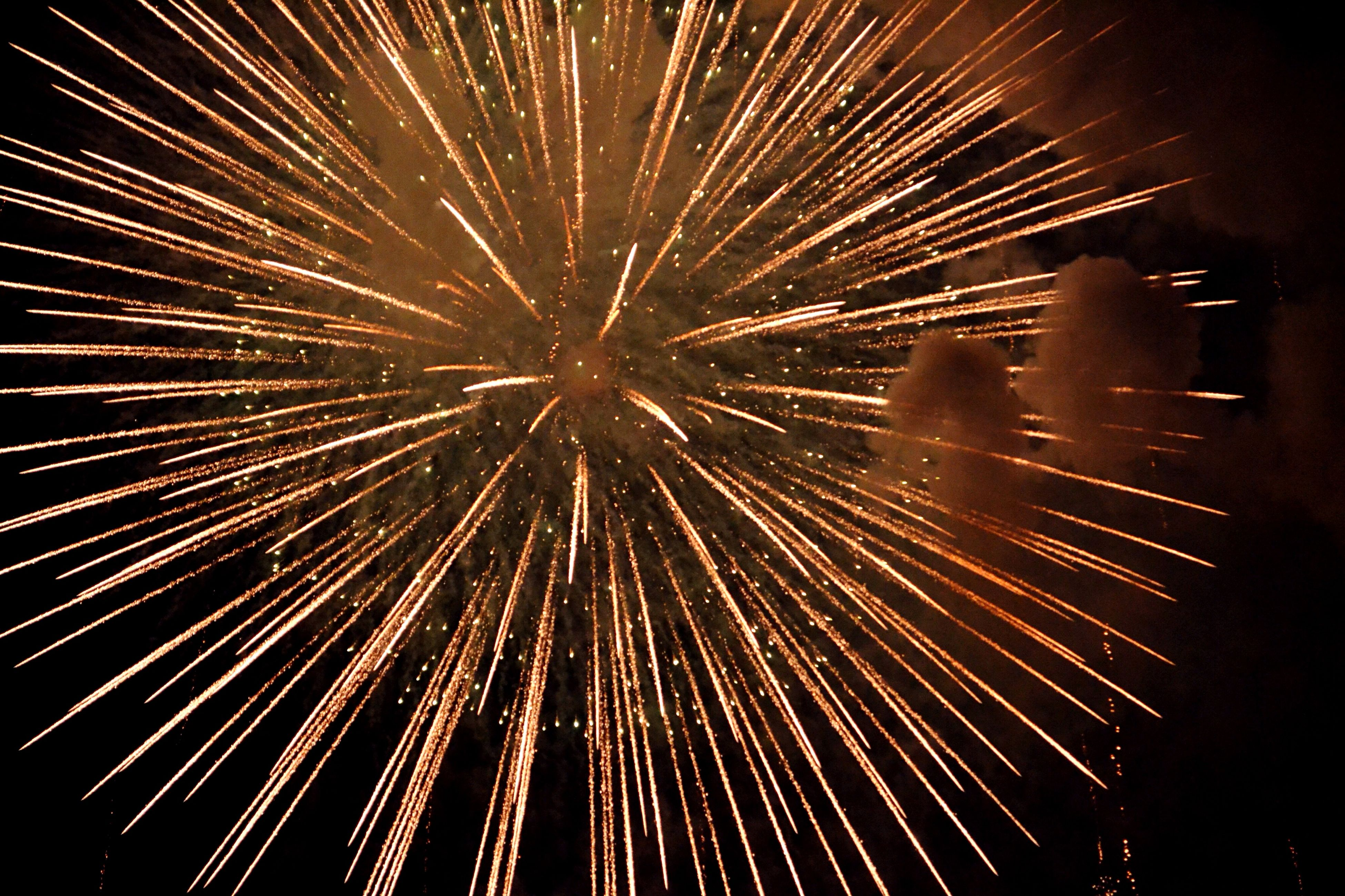 night, illuminated, firework display, celebration, exploding, arts culture and entertainment, long exposure, firework - man made object, event, motion, glowing, sparks, firework, low angle view, blurred motion, entertainment, celebration event, smoke - physical structure, fire - natural phenomenon, sky