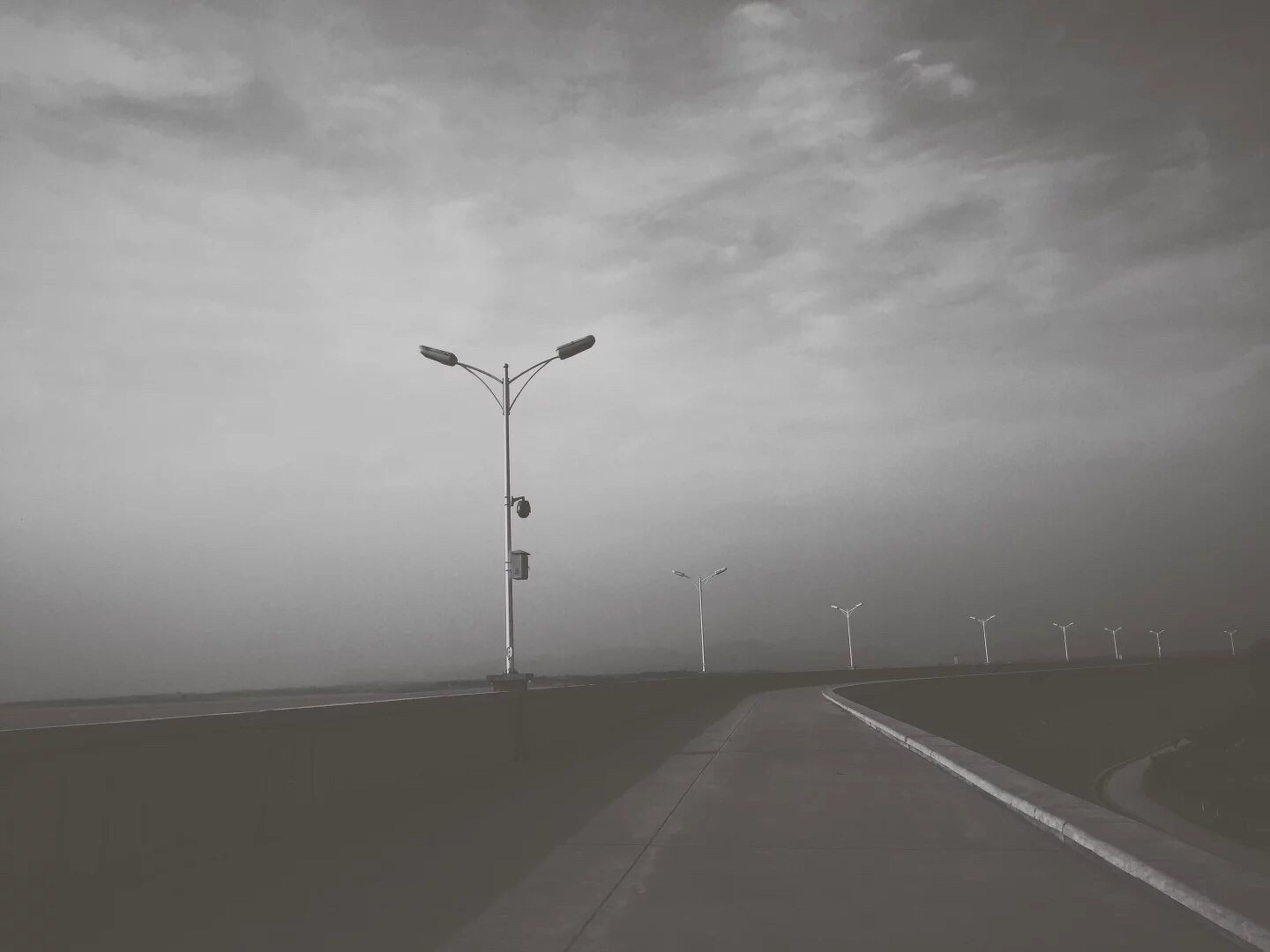 sky, the way forward, street light, cloud - sky, cloudy, weather, overcast, lighting equipment, road, built structure, diminishing perspective, cloud, nature, empty, tranquility, outdoors, street, architecture, vanishing point, railing