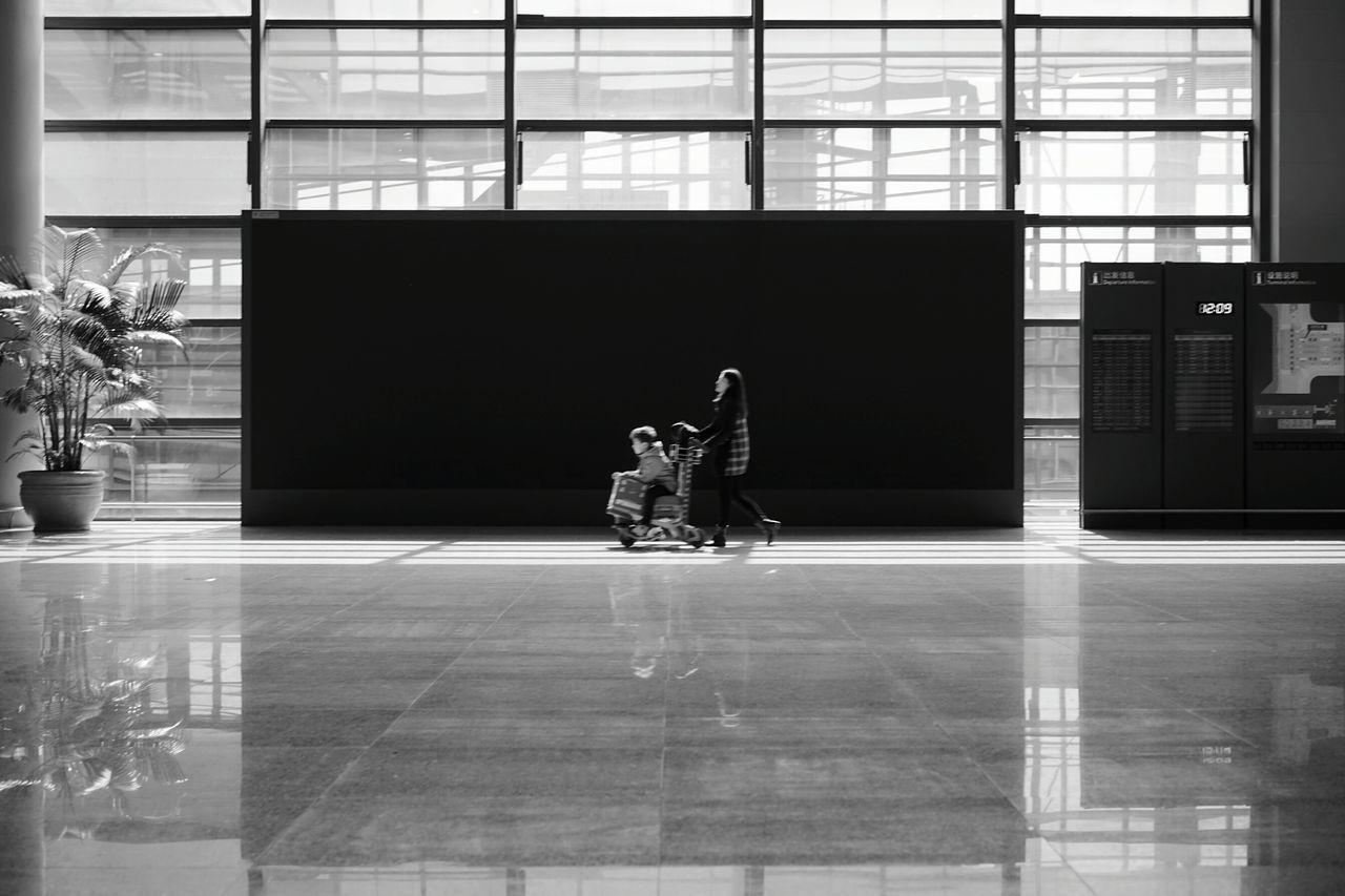 Airport Move Mother And Child Black And White Luggage Cart  Street Photographer Hi Looking At Camera The Week Of Eyeem First Eyeem Photo BEIJING北京CHINA中国BEAUTY EyeEm Best Edits My Year My View EyeEm Best Shots EyeEmNewHere Street Photography The City Light Eyeemphoto City Life Low Angle View EyeEmBestPics City Streets  EyeEm Gallery Eye4photography  Hello World