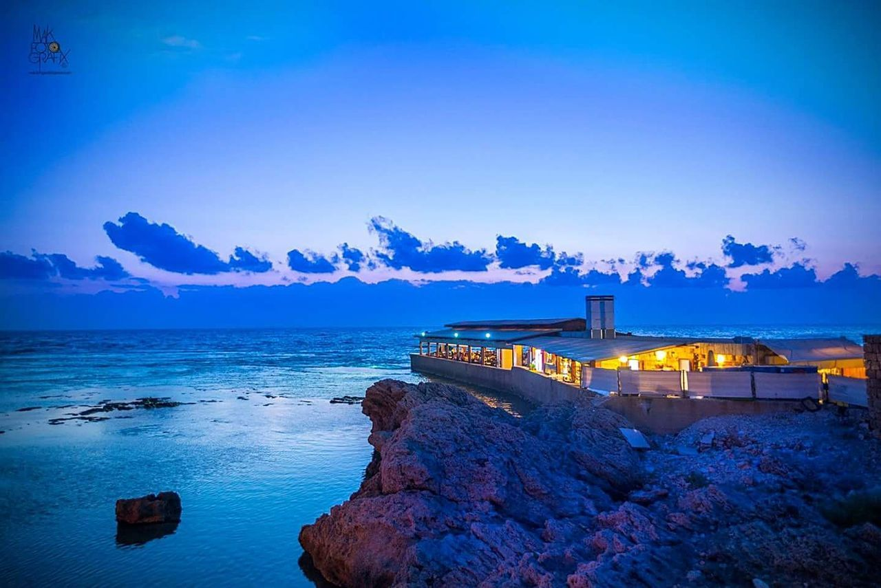 sea, sky, mountain, illuminated, blue, nature, architecture, travel destinations, scenics, no people, water, beach, outdoors, built structure, winter, beauty in nature, night, cloud - sky, tranquility, sunset, landscape, lighthouse, building exterior, snow, vacations