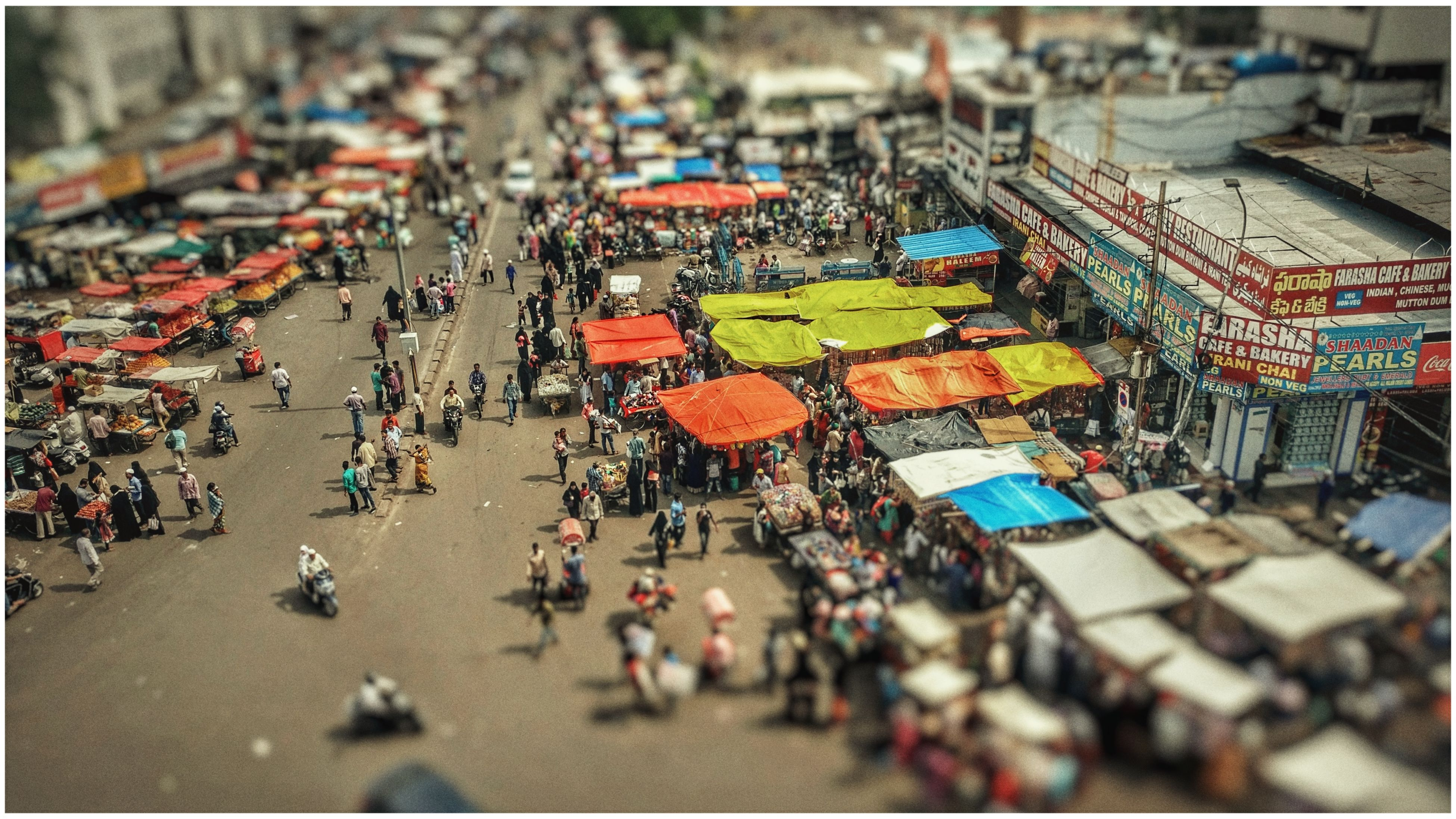 large group of people, crowded, high angle view, city, building exterior, crowd, architecture, outdoors, day, built structure, transportation, tilt-shift, real people, cityscape, people