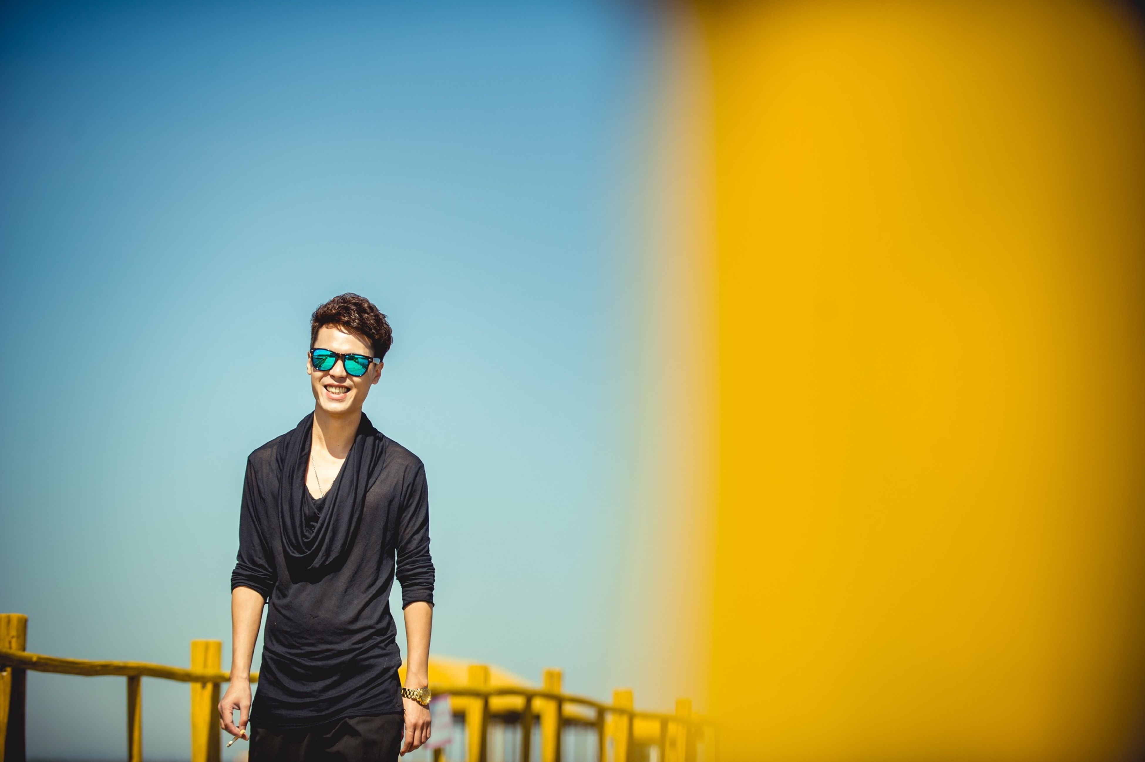 lifestyles, standing, leisure activity, young men, casual clothing, young adult, waist up, person, three quarter length, copy space, front view, portrait, looking at camera, clear sky, blue, sky, sunglasses, sunset