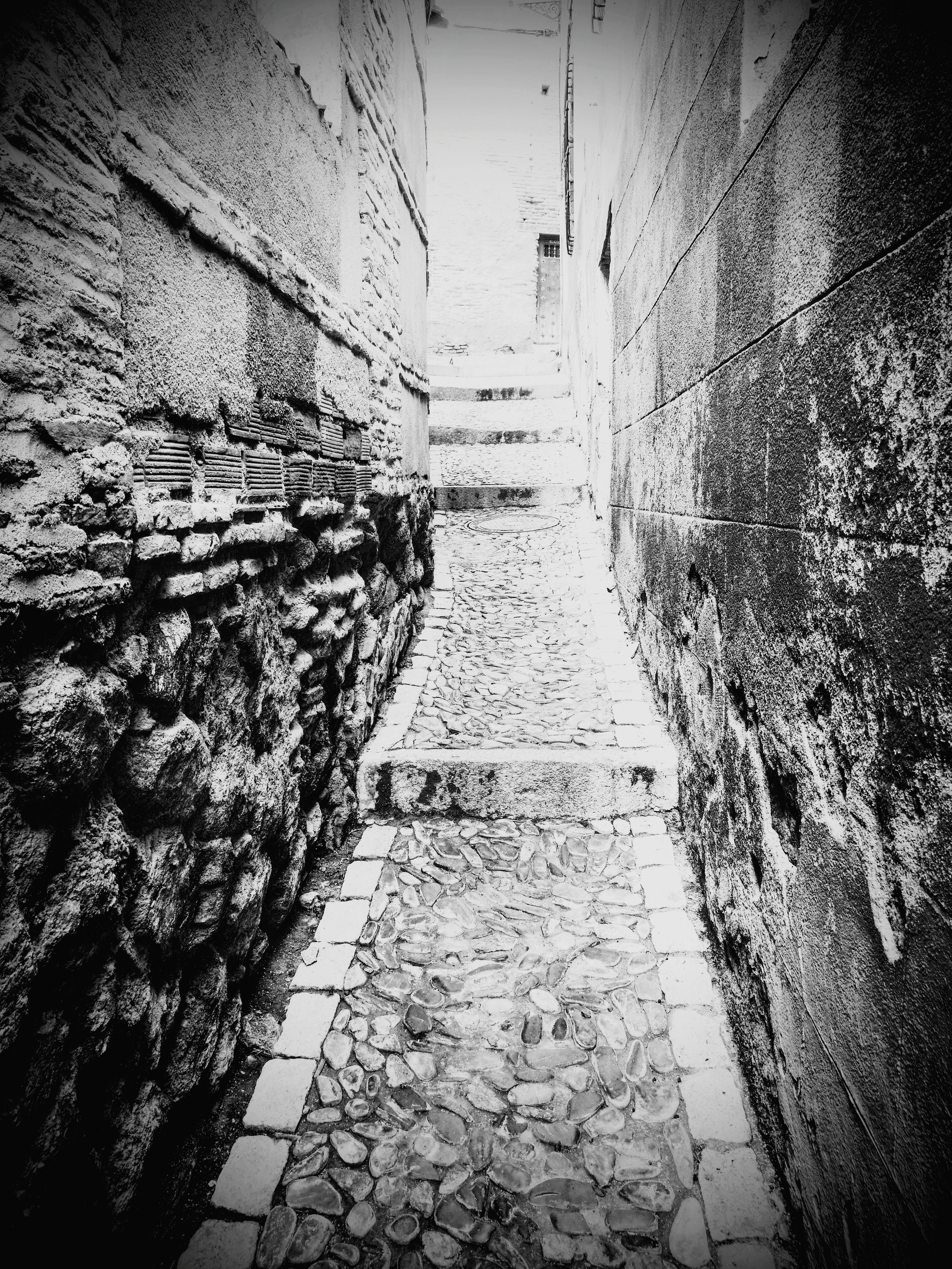 built structure, architecture, wet, the way forward, street, building exterior, transportation, rain, cobblestone, wall - building feature, day, no people, outdoors, window, paving stone, footpath, city, water, diminishing perspective