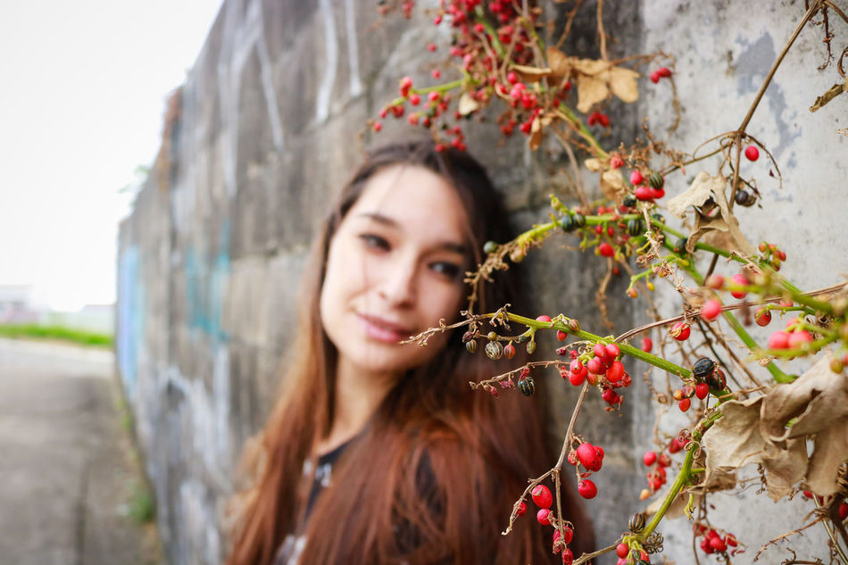 Beautiful Woman Beauty Day Flower Happiness Headshot Leisure Activity Lifestyles Long Hair Looking At Camera Nature One Person One Young Woman Only Only Women Outdoors Plant Portrait Real People Red Smiling Standing Tree Women Young Adult Young Women