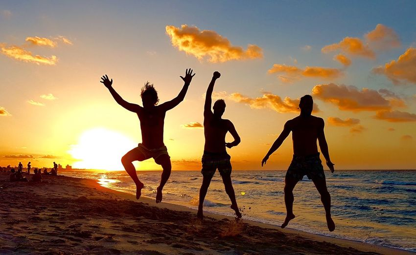 Uniqueness Spend Time With Friends Beach Sunset Sea Sky Silhouette Lifestyles Horizon Over Water Fun Water Friendship Arms Raised Real People Enjoyment Leisure Activity Vacations Togetherness Happiness Full Length Jumping