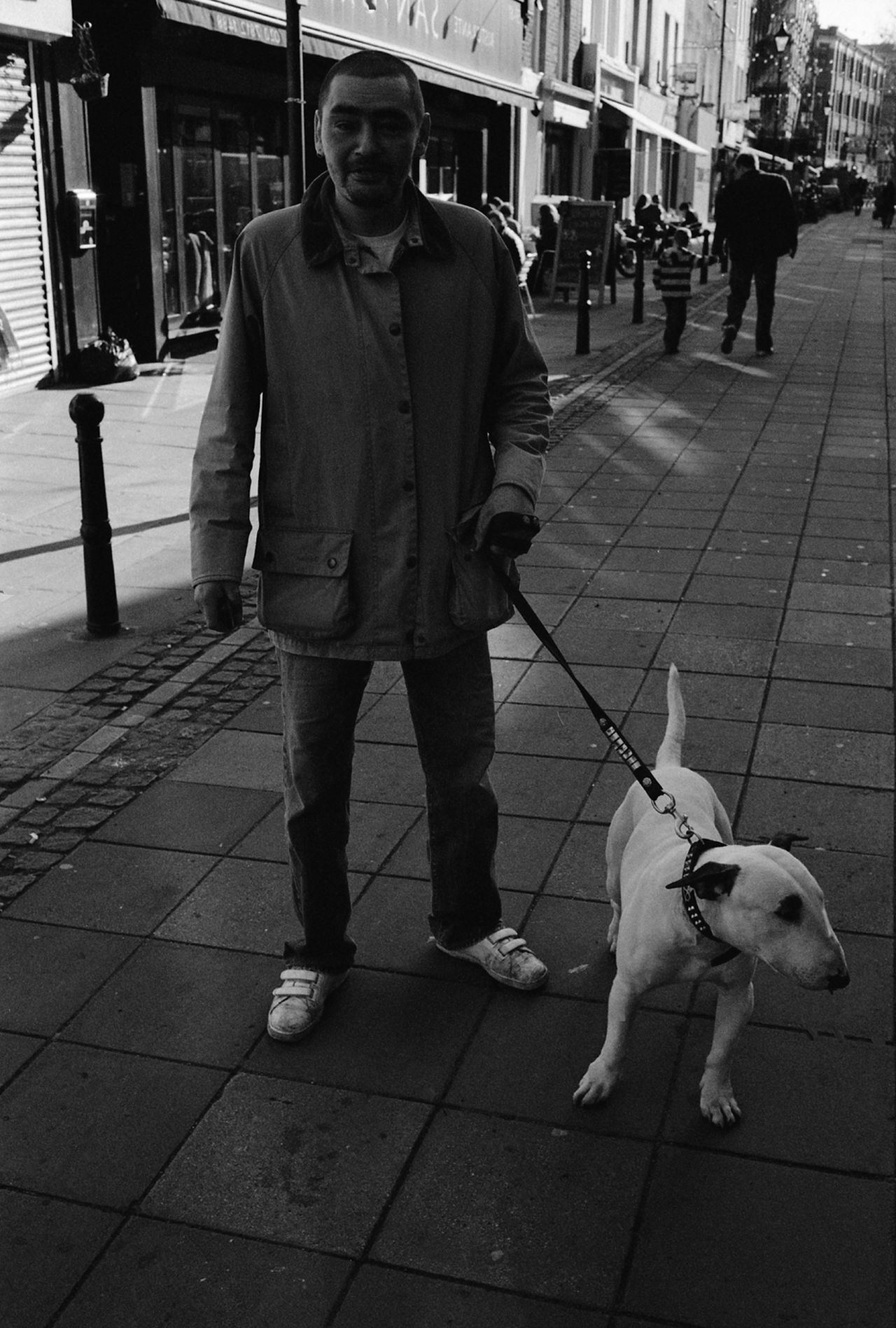 Gentleman of the Road with his Bull Terrier Lucy Alone Casual Clothing Friendship Front View Full Length Gentleman Of The Road With Bull Terrier Soho London Holding Leisure Activity Lifestyles Men Occupation Perspective Portrait Real People Relaxation Sitting Standing Togetherness Walking Women Young Adult