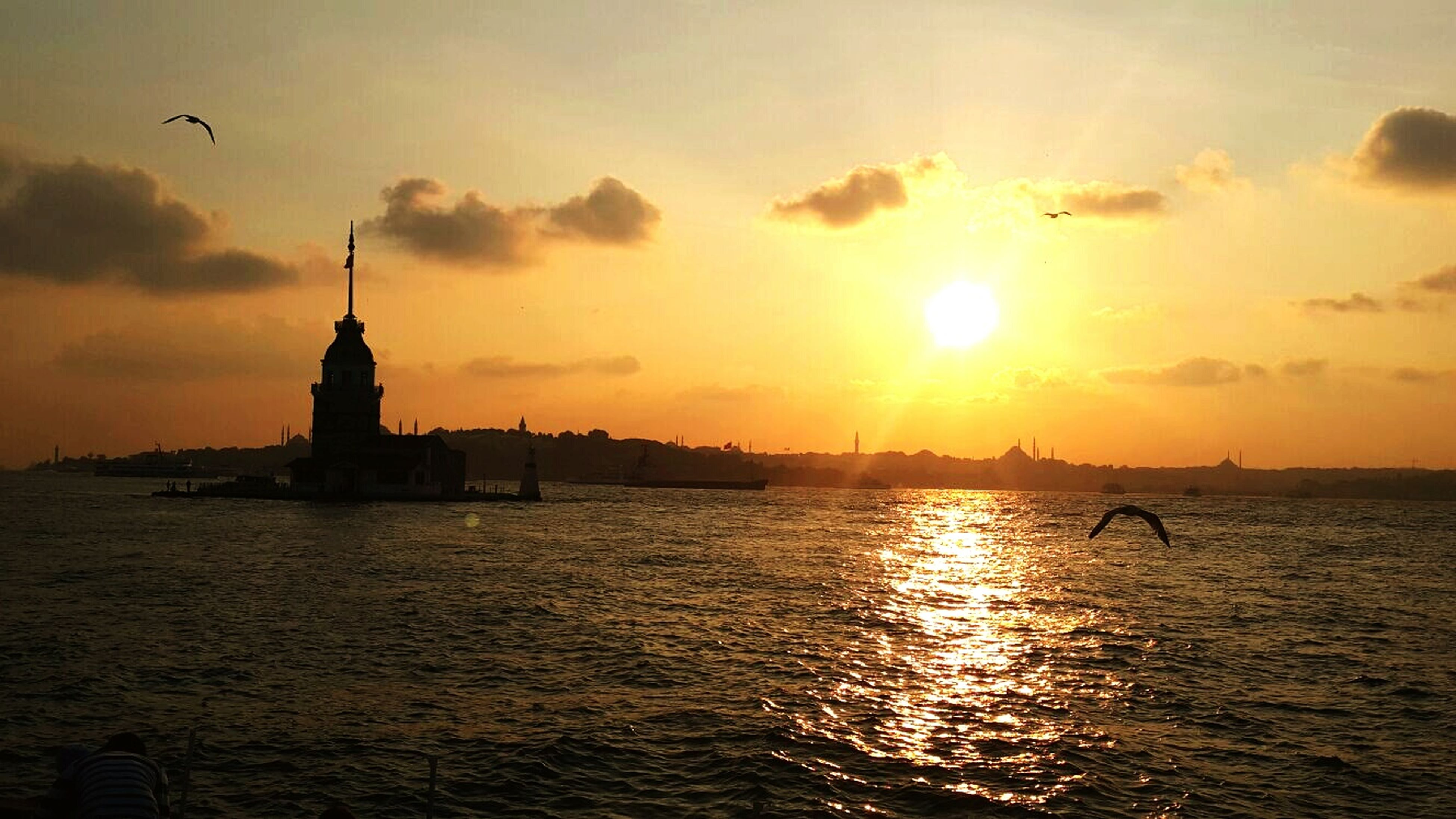 sunset, water, sun, silhouette, sea, sky, waterfront, orange color, scenics, built structure, architecture, building exterior, beauty in nature, tranquil scene, rippled, tranquility, reflection, bird, sunlight, nature